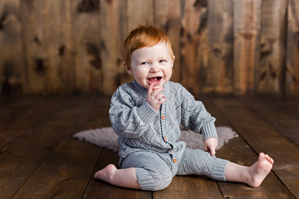 Baby boy sitter session with grey quilted romper on wood background.