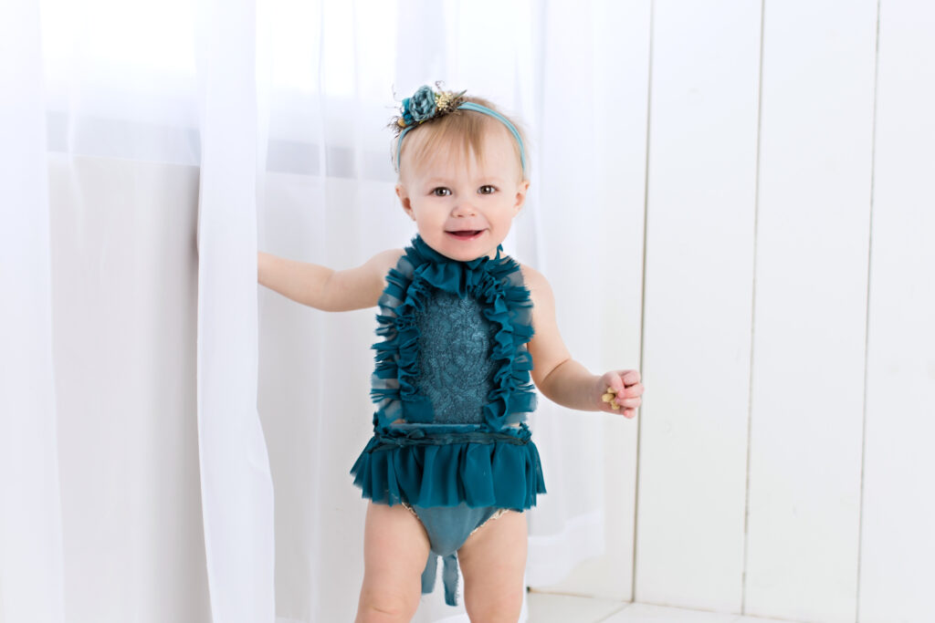 Baby girl sitter session with teal romper and garden tieback with flowing white curtain and white wood background.