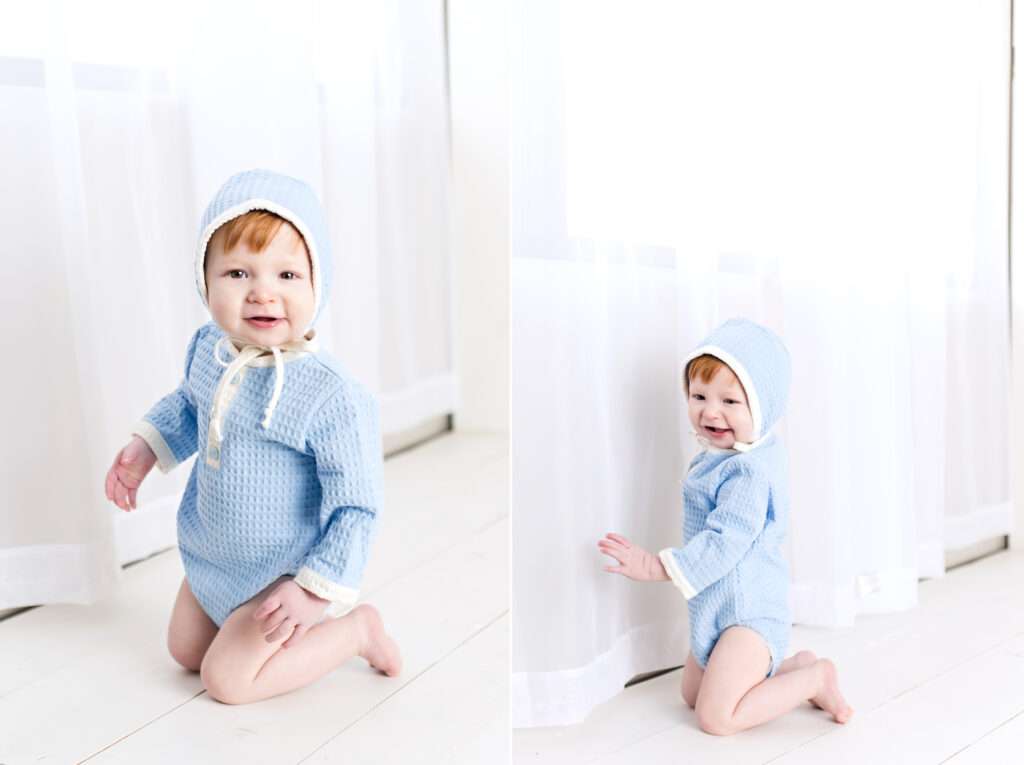 Baby boy sitter session with light blue romper and bonnet with flowing white curtain and white wood background.