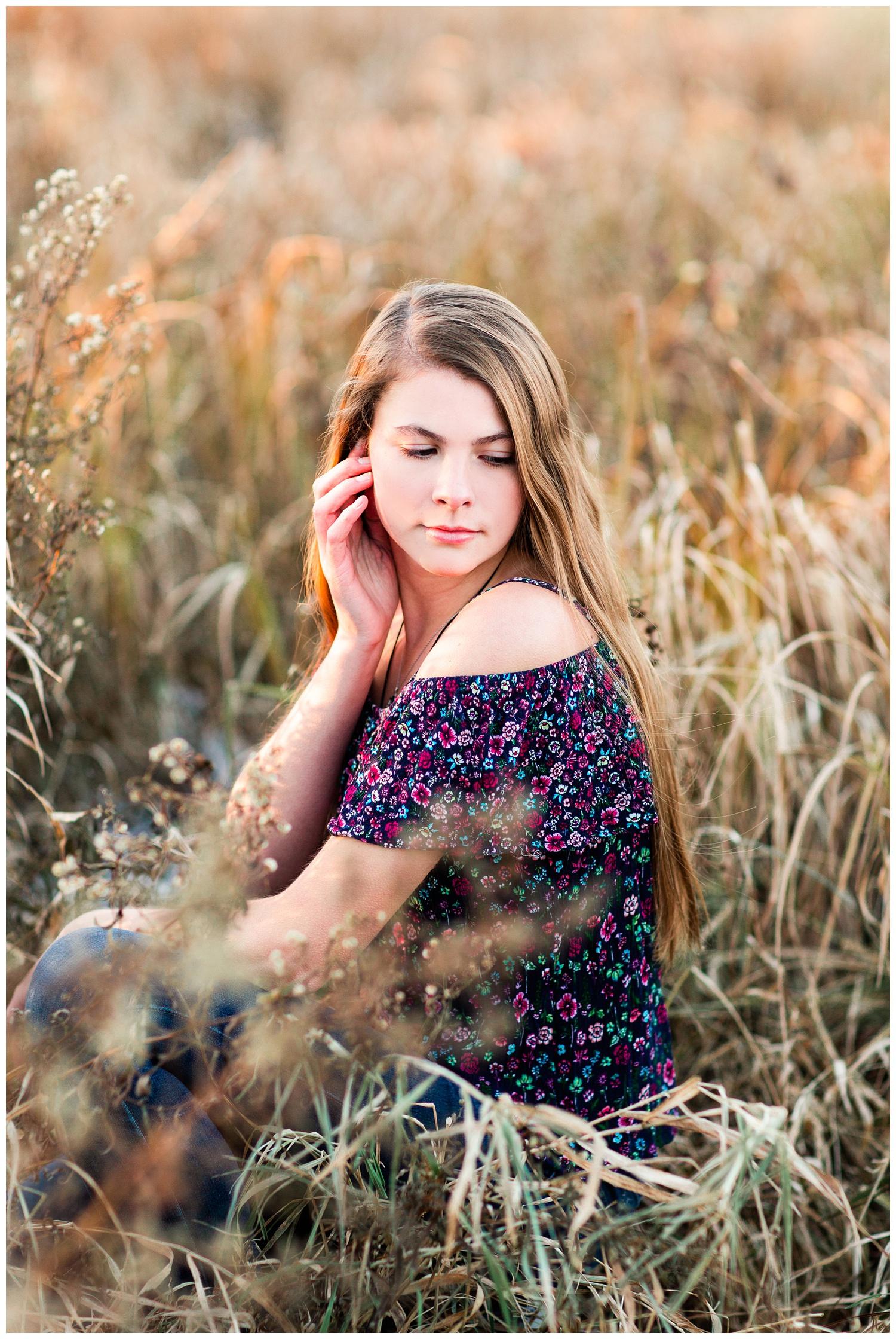 Iowa Senior girl sitting in a fall grassy field in Algona, Iowa