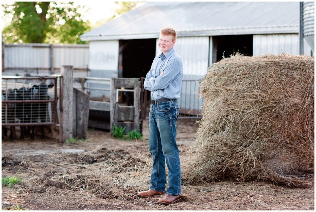 Senior photo by hay bales and cattle cows | Farm senior session | Iowa Senior Photographer | CB Studio