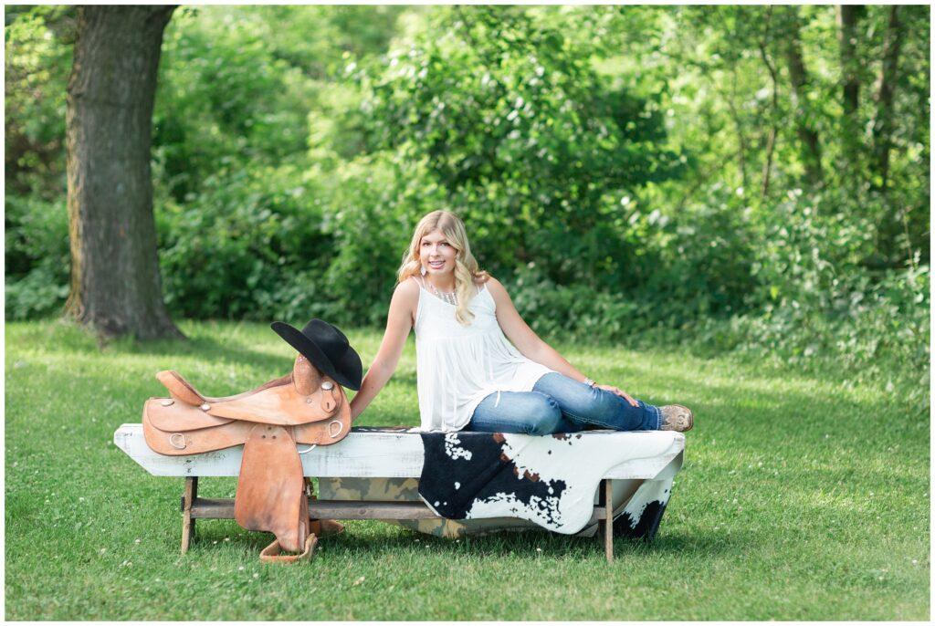 Senior portrait session at a park during golden hour   Senior girl poses with horse props   Iowa Senior Photographer   CB Studio