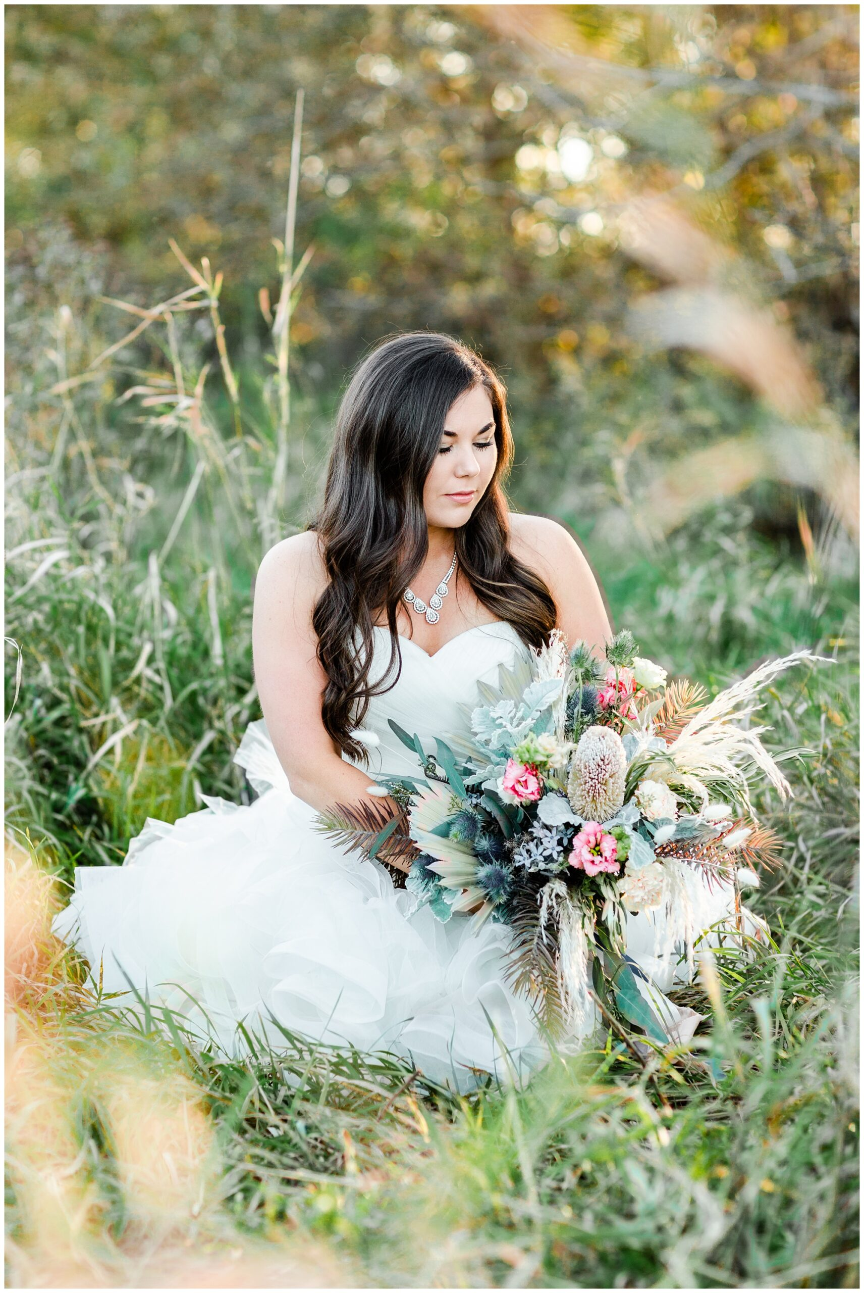 Bridal portrait sitting in a field with a large bouquet with soft florals