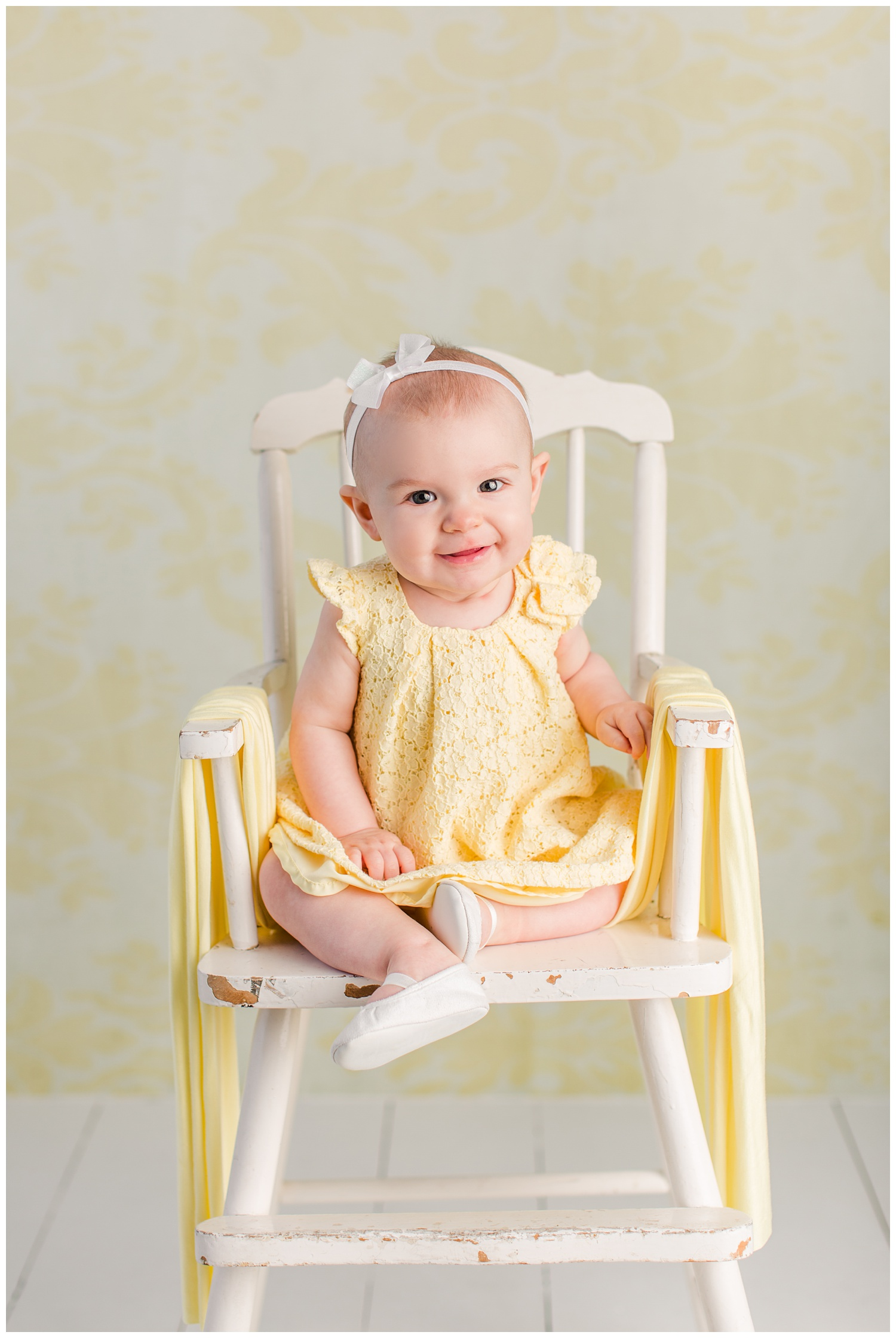 Baby Nora poses in her yellow eyelet Easter dress in an antique high chair.