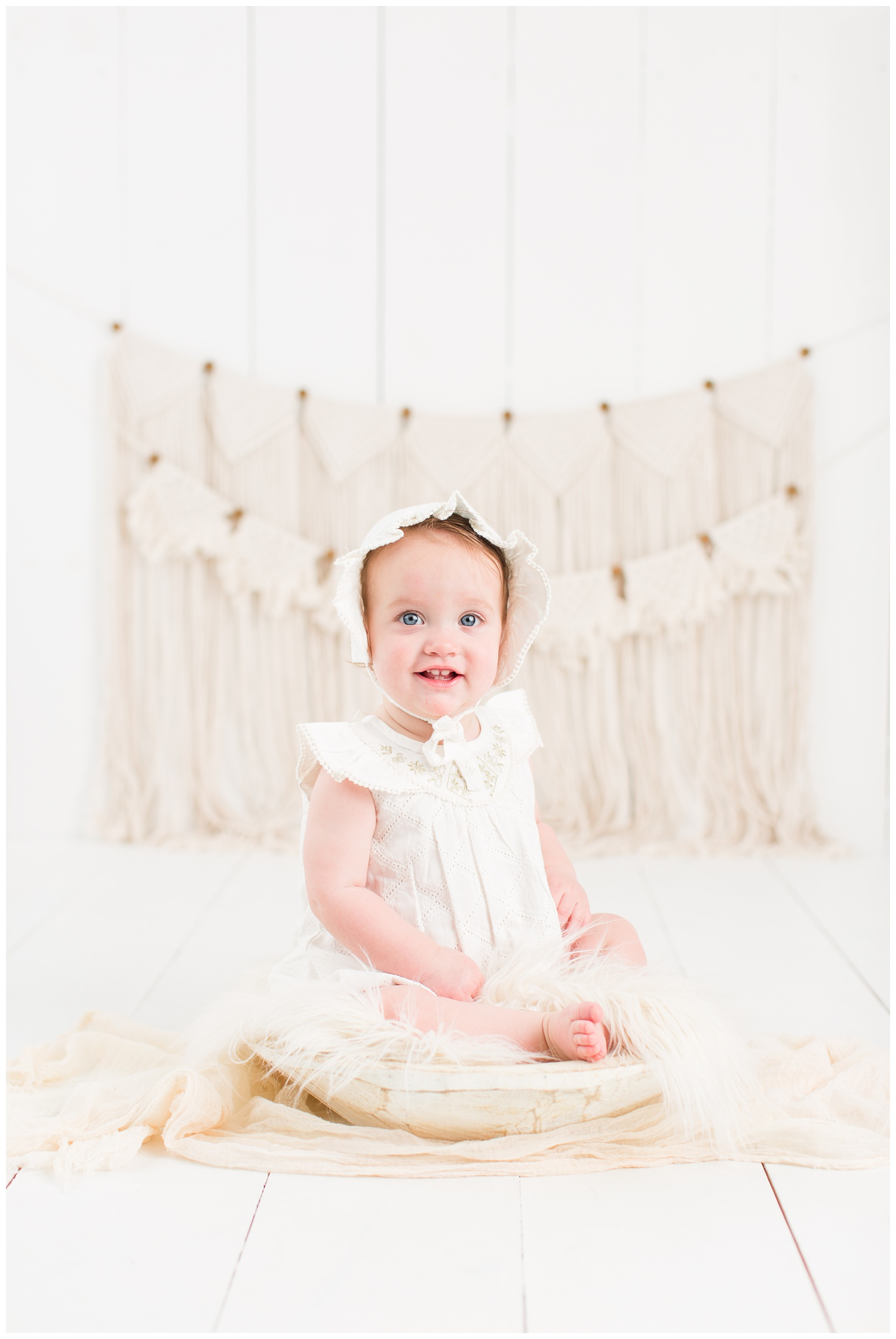 Baby Cara dressed in a vintage white romper and bonnet sitting in a rustic cream bowl with a boho macrame background | CB Studio