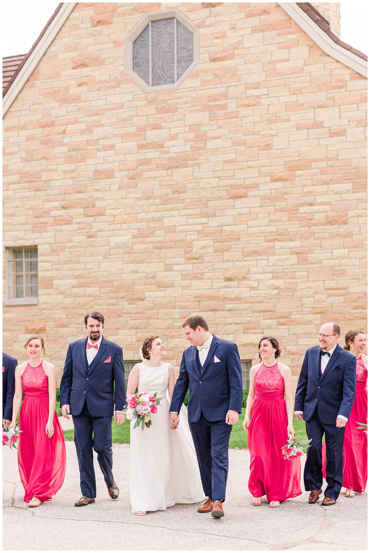 Wedding party wearing navy and Valentine pink walk away from a church in Algona Iowa | CB Studio