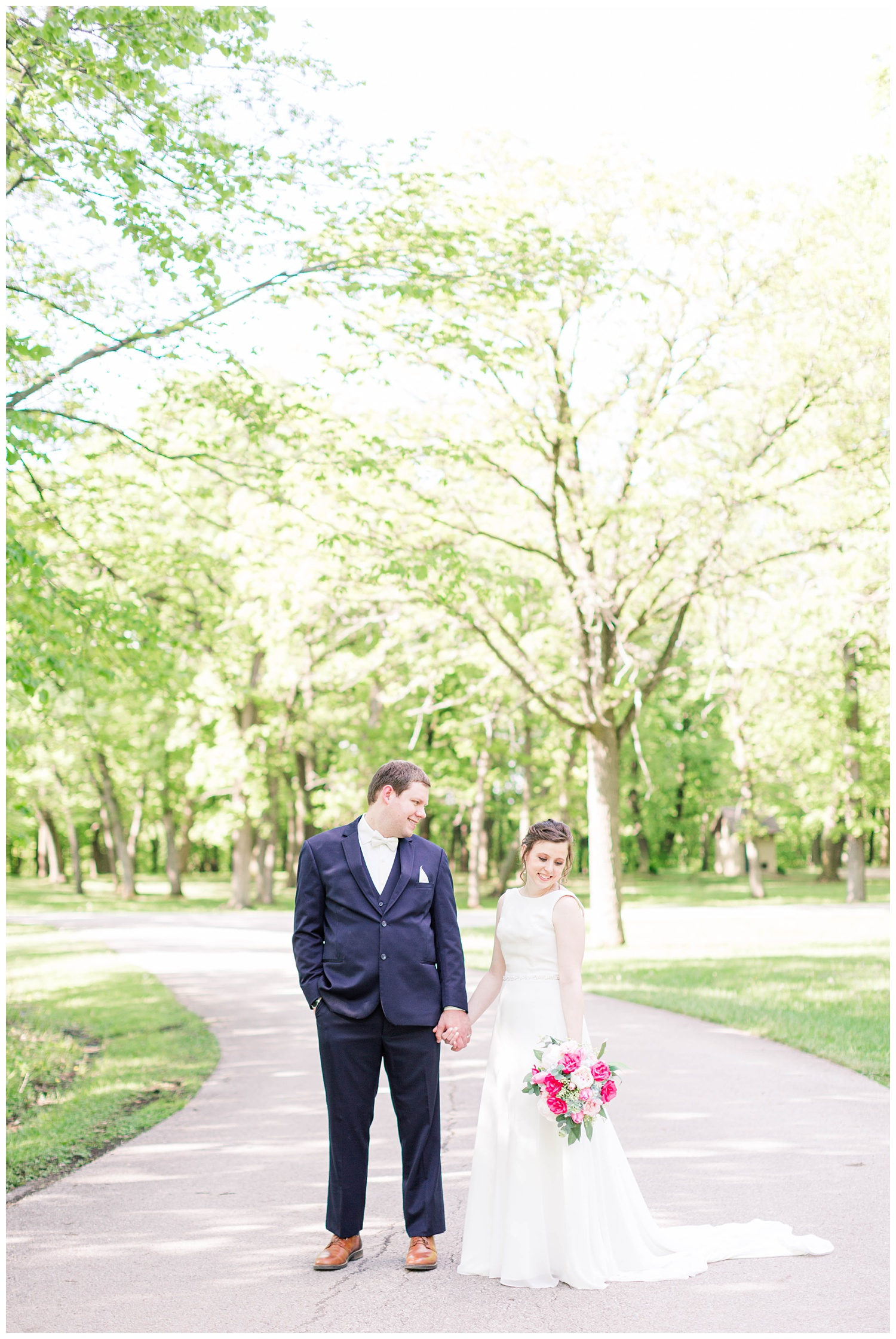 Bride and groom hold hands on a scenic path in Call Park Algona Iowa | CB Studio