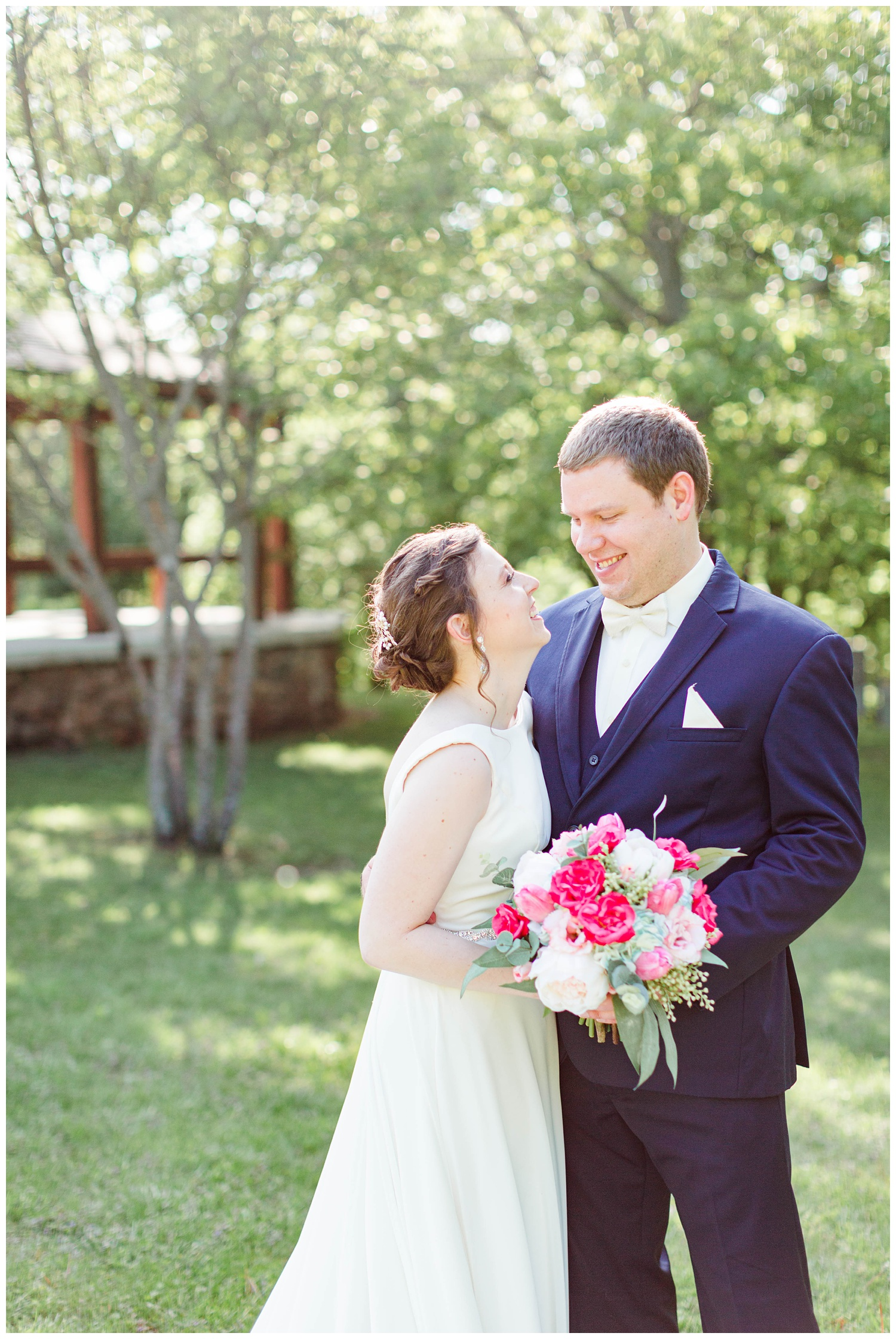 Bride and groom look at each other with a scenic view in Call Park Algona Iowa | CB Studio
