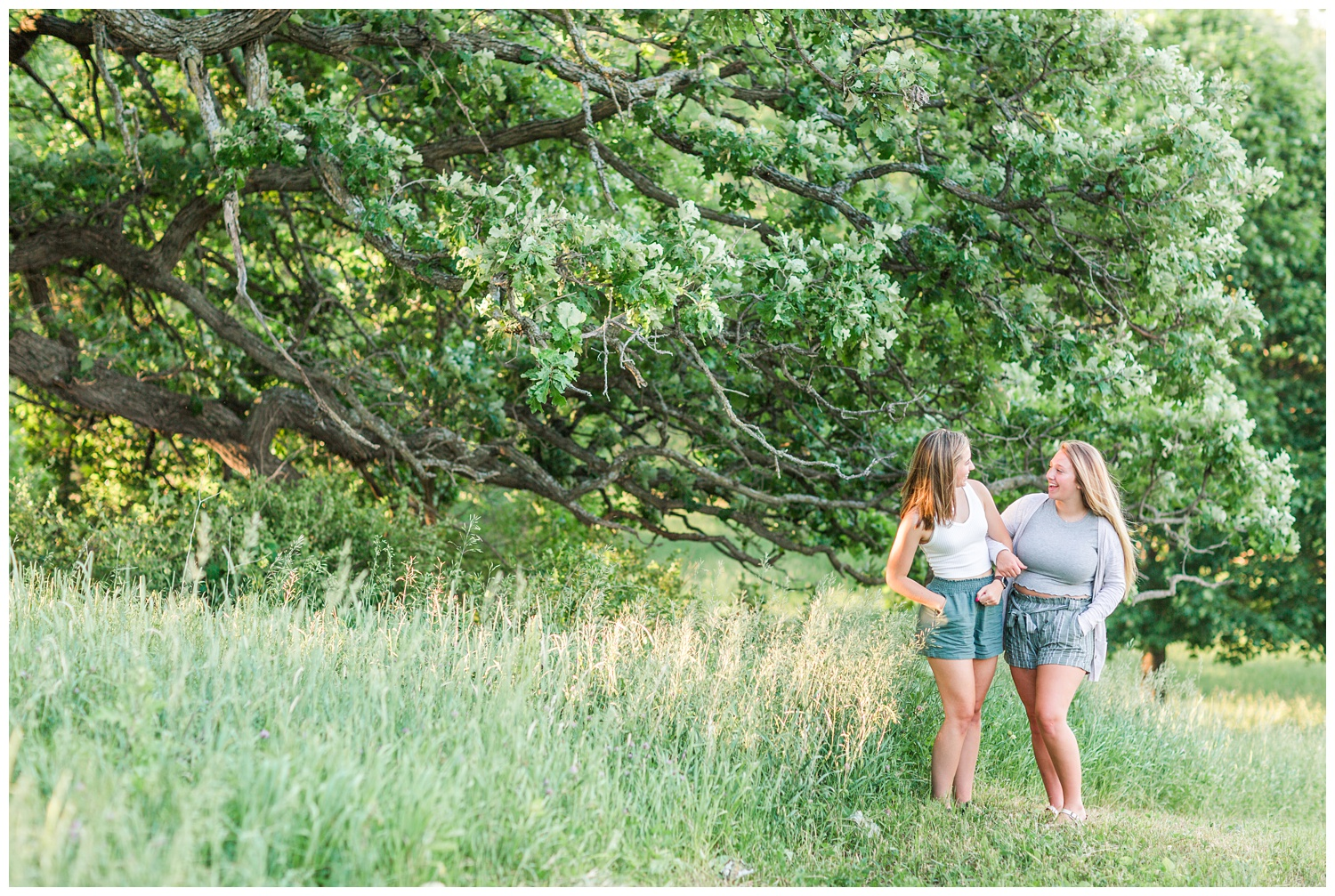 Senior girls best friends BFFs embrace laughing at each other in a grassy field on a rural Iowa farm | CB Studio