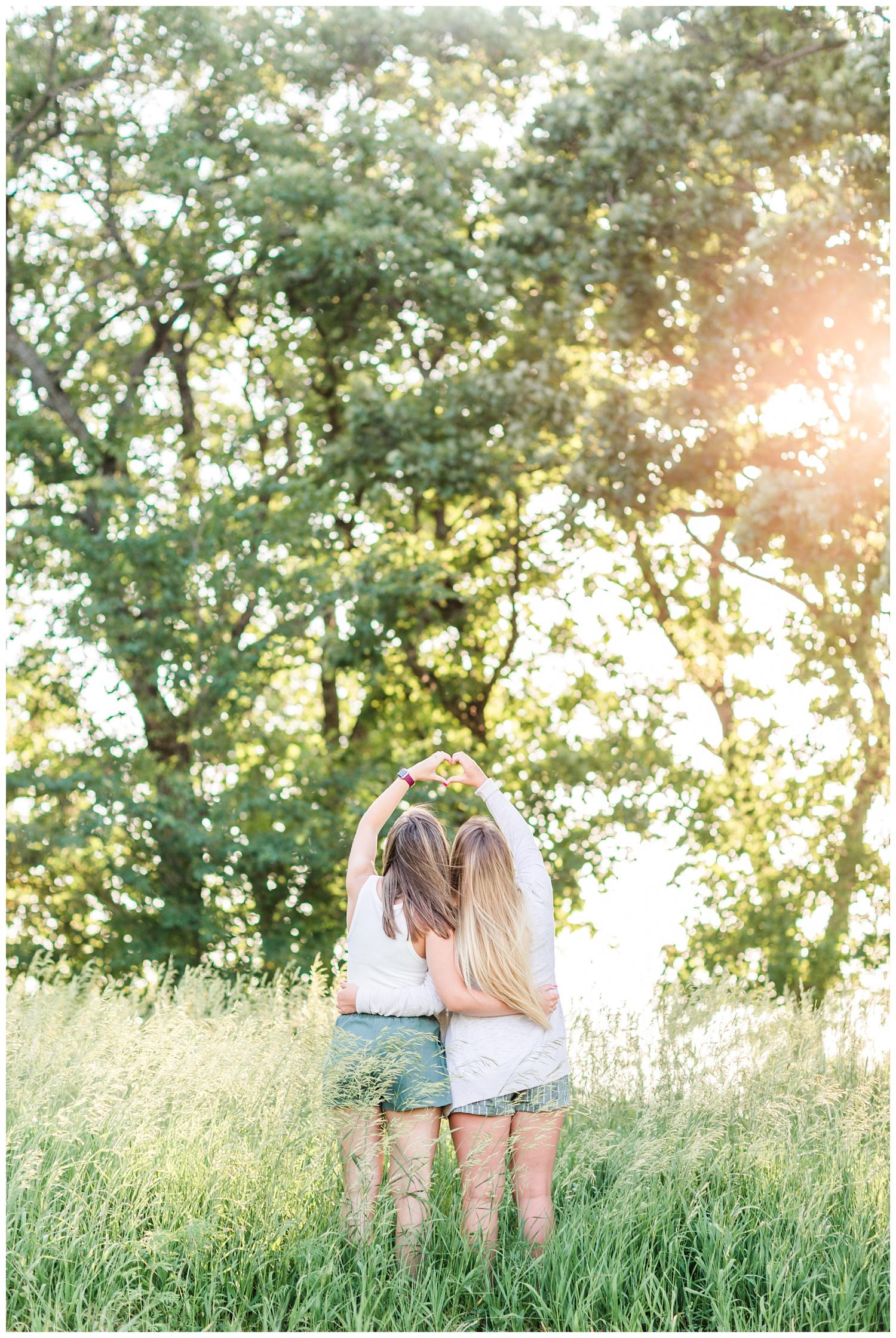 Senior girls best friends BFFs make a heart symbol with their hands in a grassy field on a rural Iowa farm | CB Studio