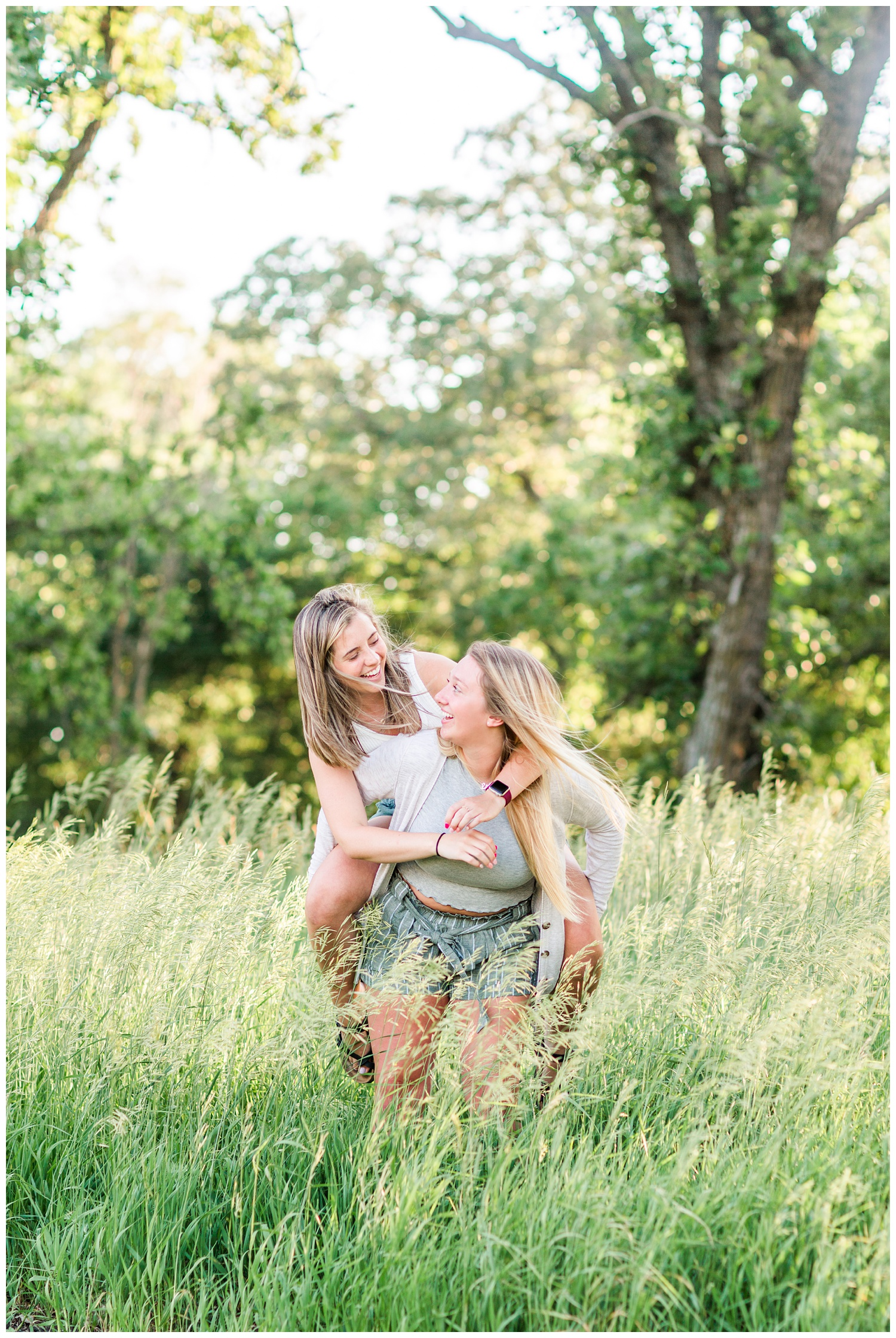 Senior girls best friends BFFs piggy back while laughing in a grassy field on a rural Iowa farm | CB Studio
