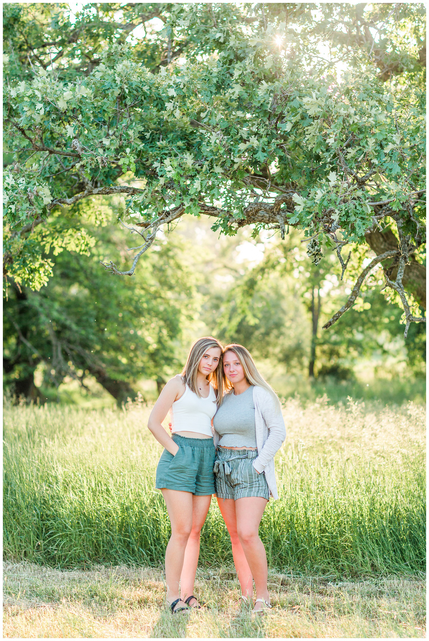 Senior girls best friends BFFs embrace in a grassy field on a rural Iowa farm with glowing, bright and airy lighting | CB Studio
