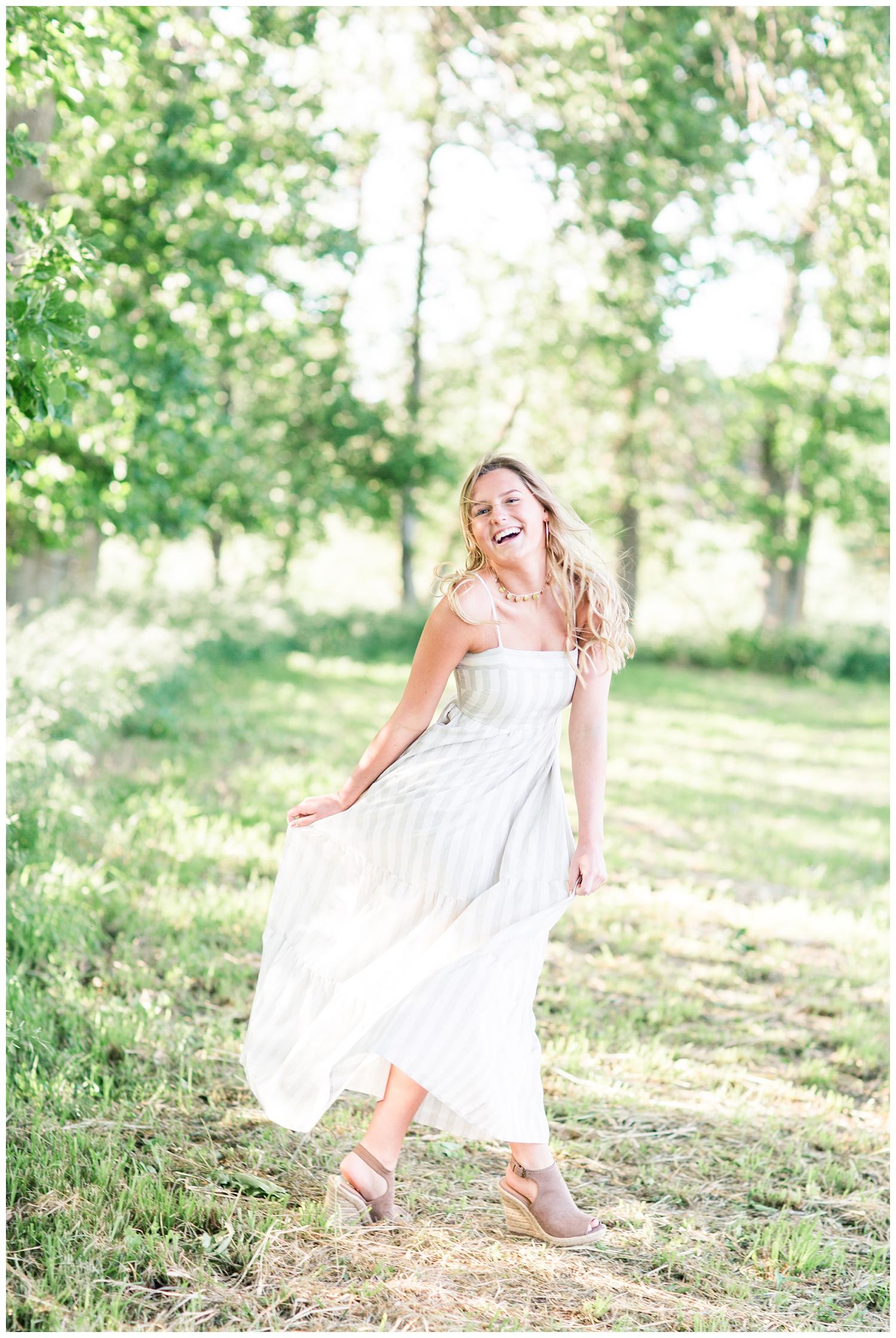 Senior girl dances in a grassy field wearing a flowing white summer dress | CB Studio