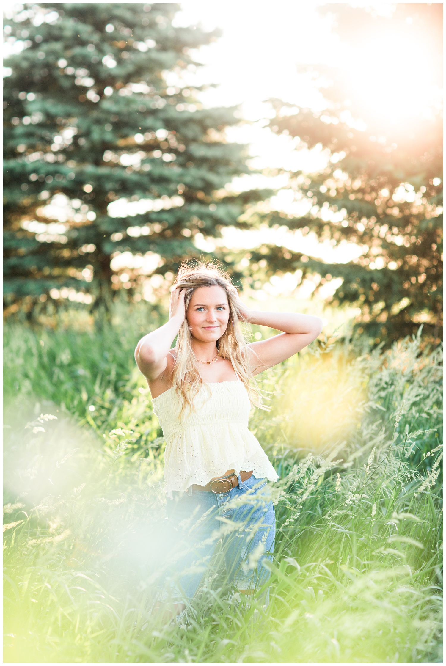 Senior girl wearing a yellow eyelet tank top standing in a grassy field with her hands in her hair. | CB Studio