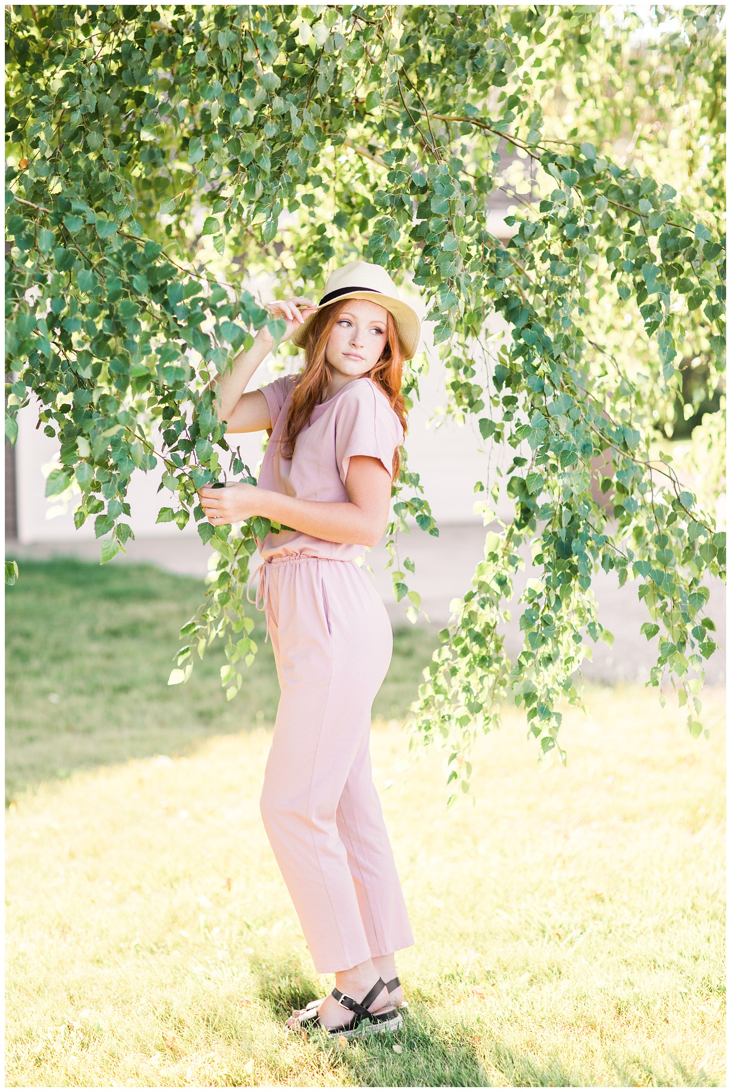 Senior girl wearing a dusty pink jumpsuit and a straw hat looking over her shoulder surrounded by birch tree branches in West Bend, Iowa | CB Studio