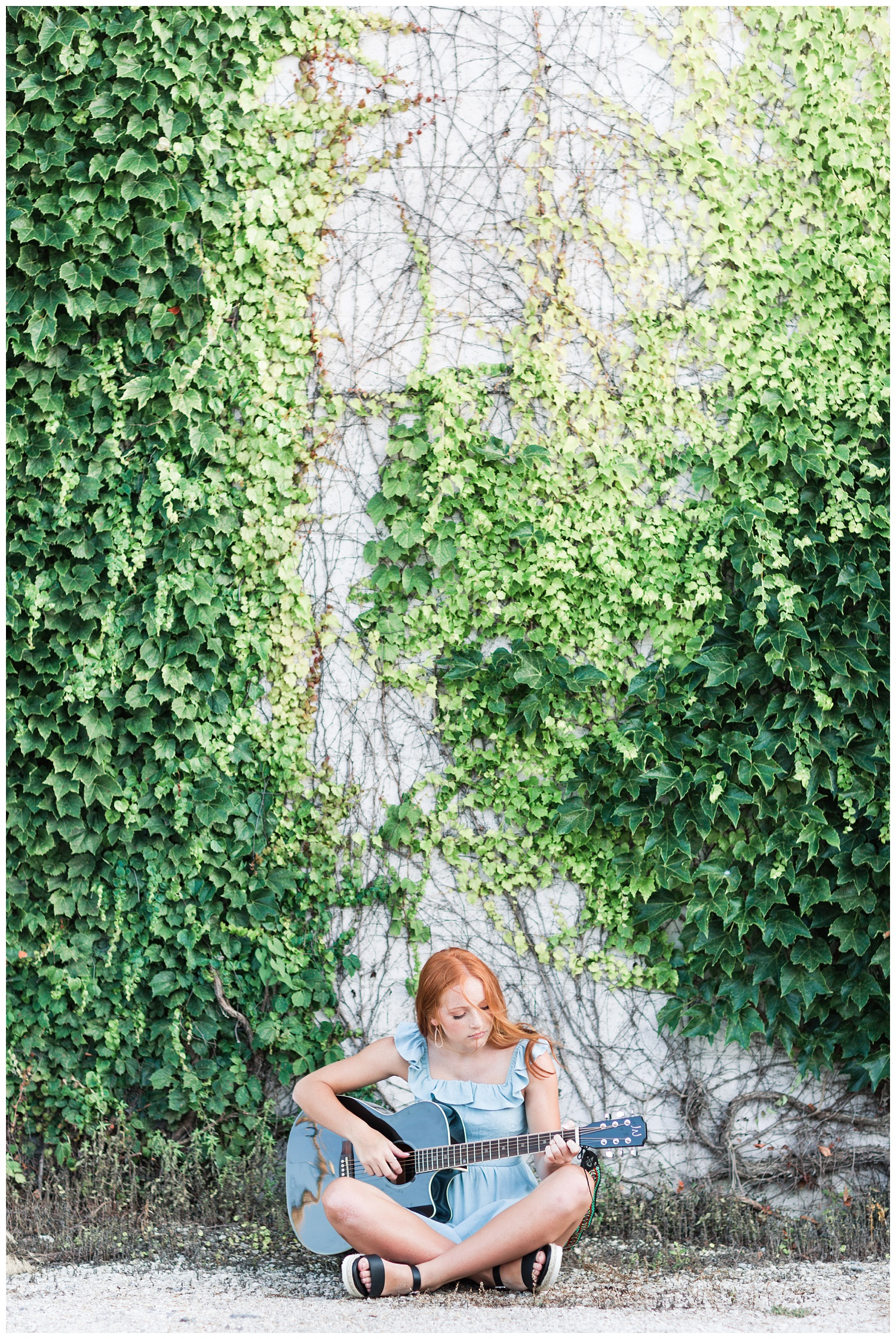 Senior girl sitting next to a green vine wall playing guitar in West Bend, Iowa | CB Studio