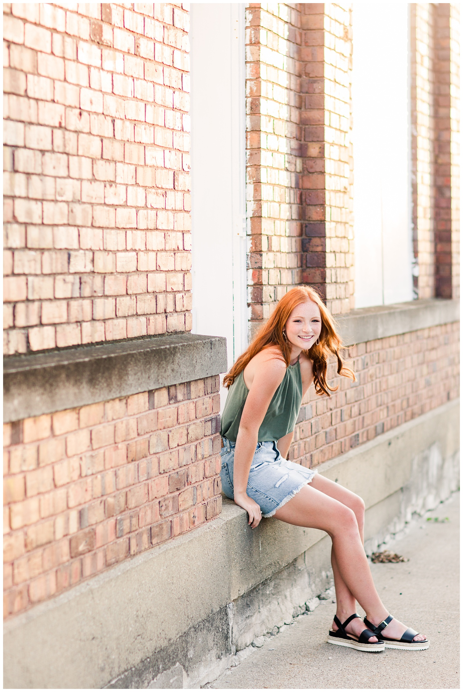 Senior girl sitting on a step next to a brick building during golden hour as the breeze blows through her hair in West Bend, Iowa | CB Studio