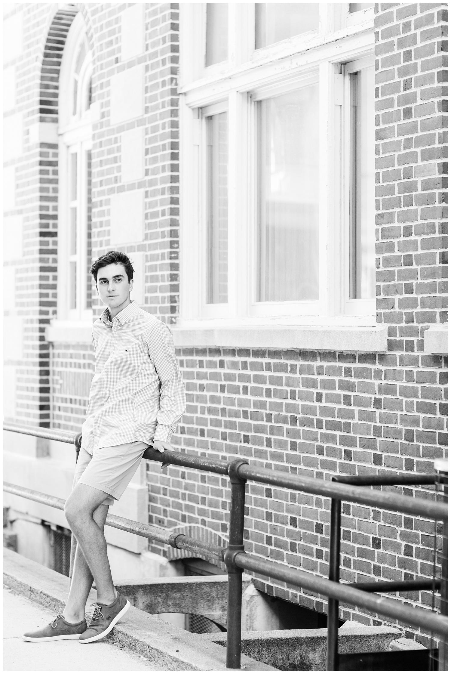 Senior boy leans against a railing next to a historic building in downtown Algona, Iowa | CB Studio