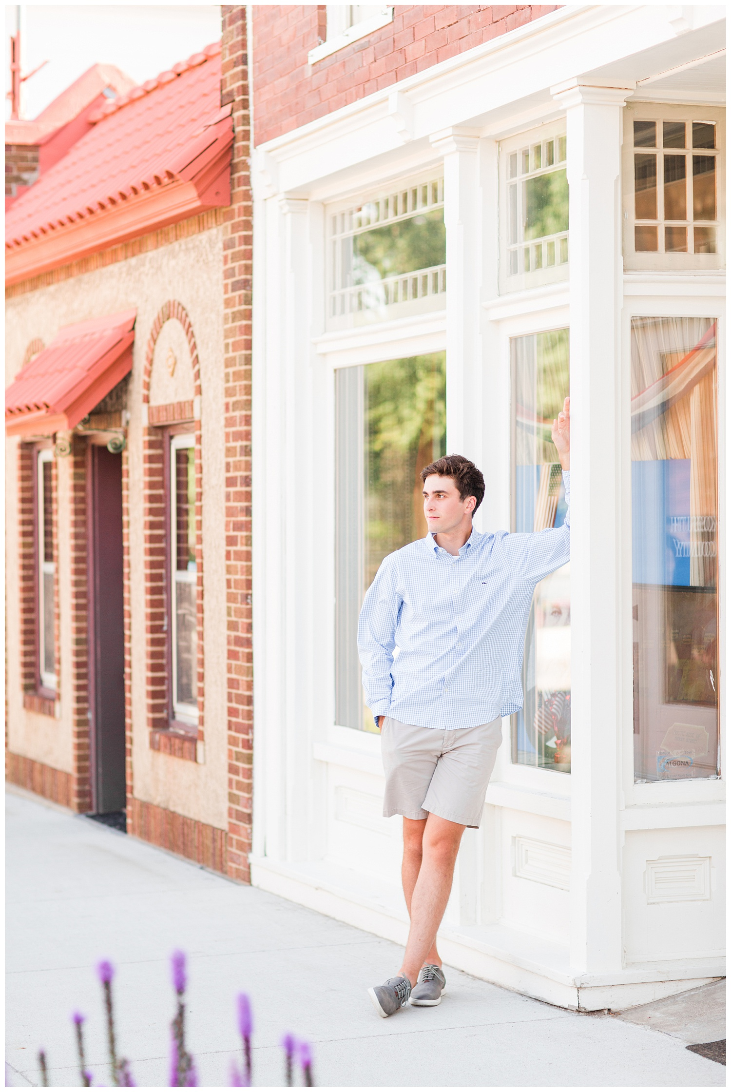 Senior boy leans against historic building in downtown Algona, Iowa | CB Studio