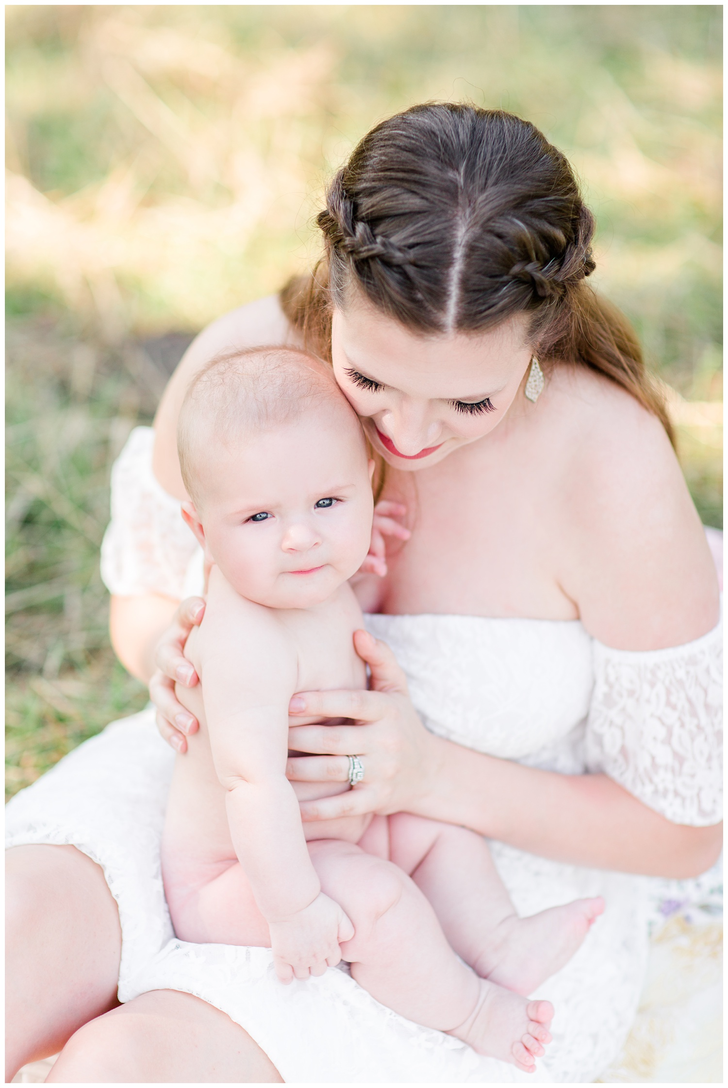 Beautiful mama wearing a white lacy dress sits in a glowy, grassy field snuggling her smiling baby boy | CB Studio