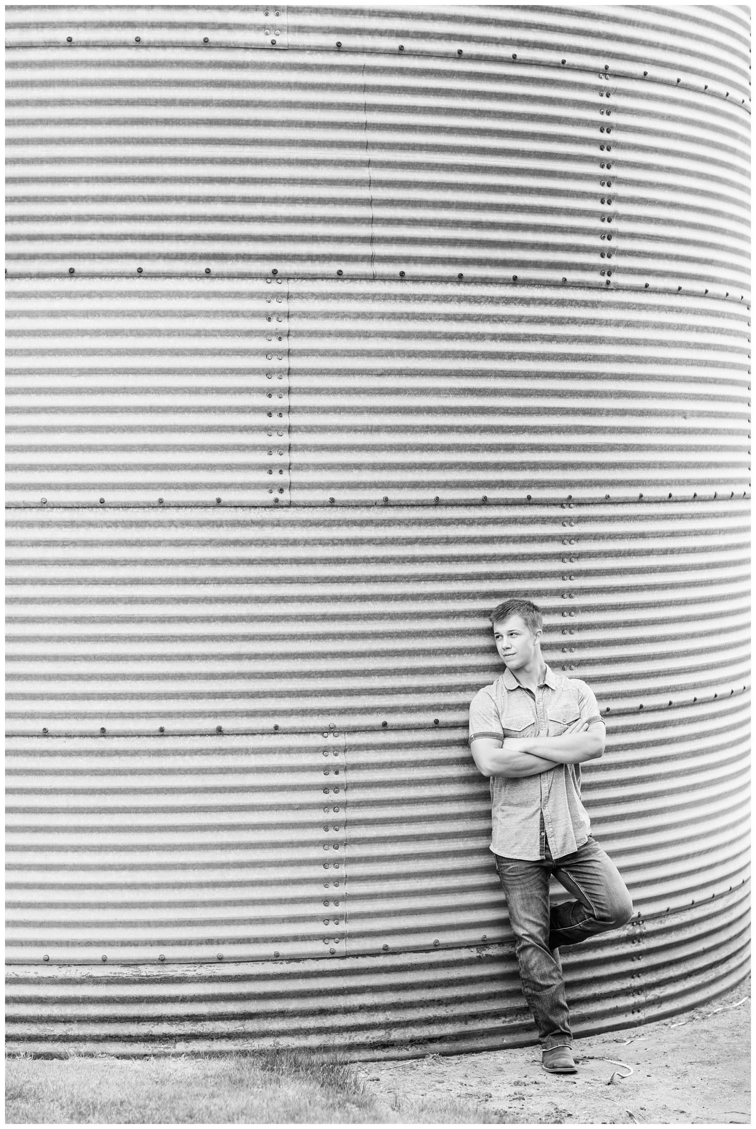 Senior boy leans against a grain bin a on rural Iowa farm   CB Studio