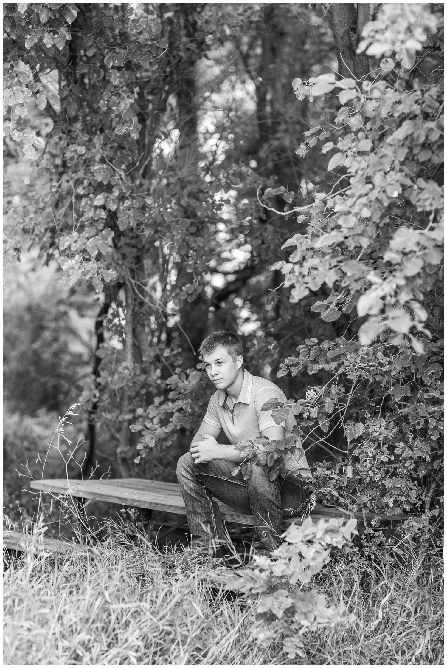 Senior boy sits on an old picnic bench tuck inside the woods a on rural Iowa farm   CB Studio