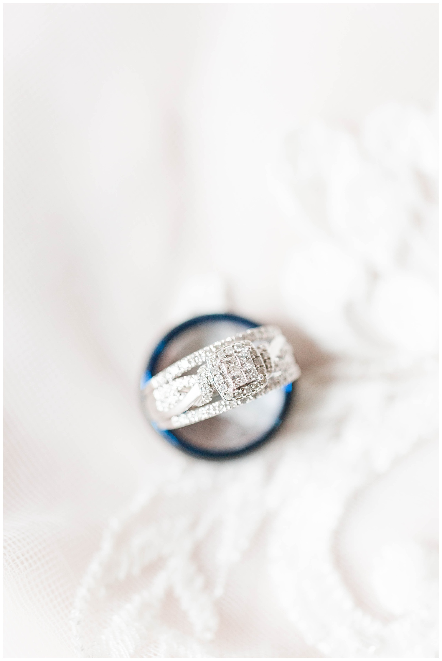 Bridal wedding band and groom's ring delicately placed on the lace of a wedding dress.   CB Studio
