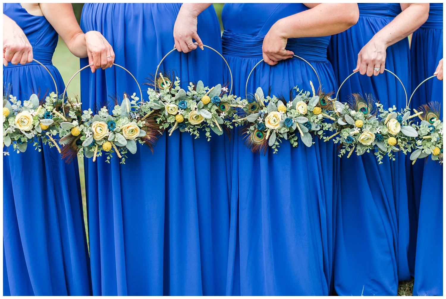 Royal blue and yellow hoop bouquets featuring peacock feathers.   CB Studio