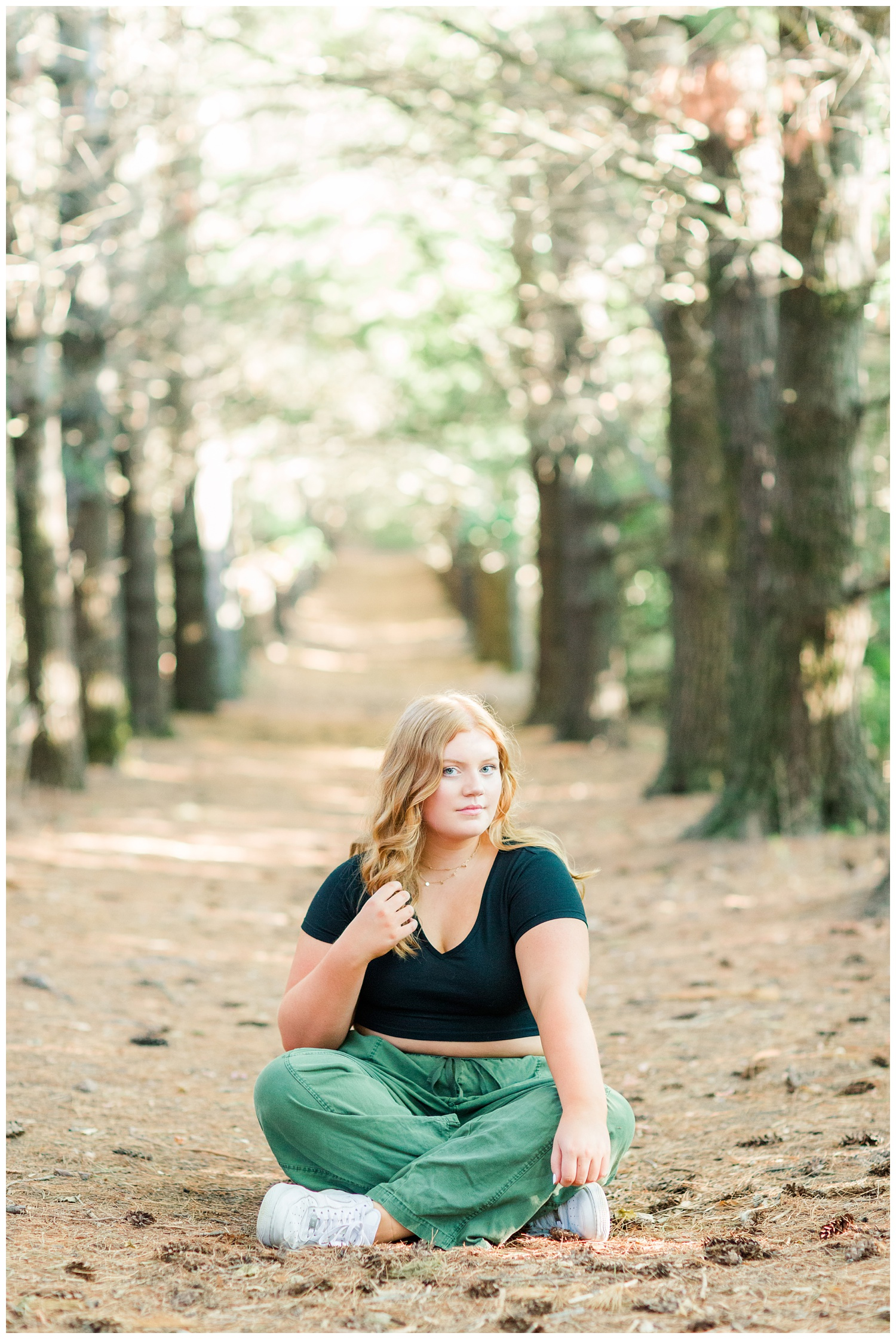 Senior girl wearing a black crop top and green cargo pants sitting beneath a row of pines at Water's Edge Nature Center in Algona, Iowa | CB Studio