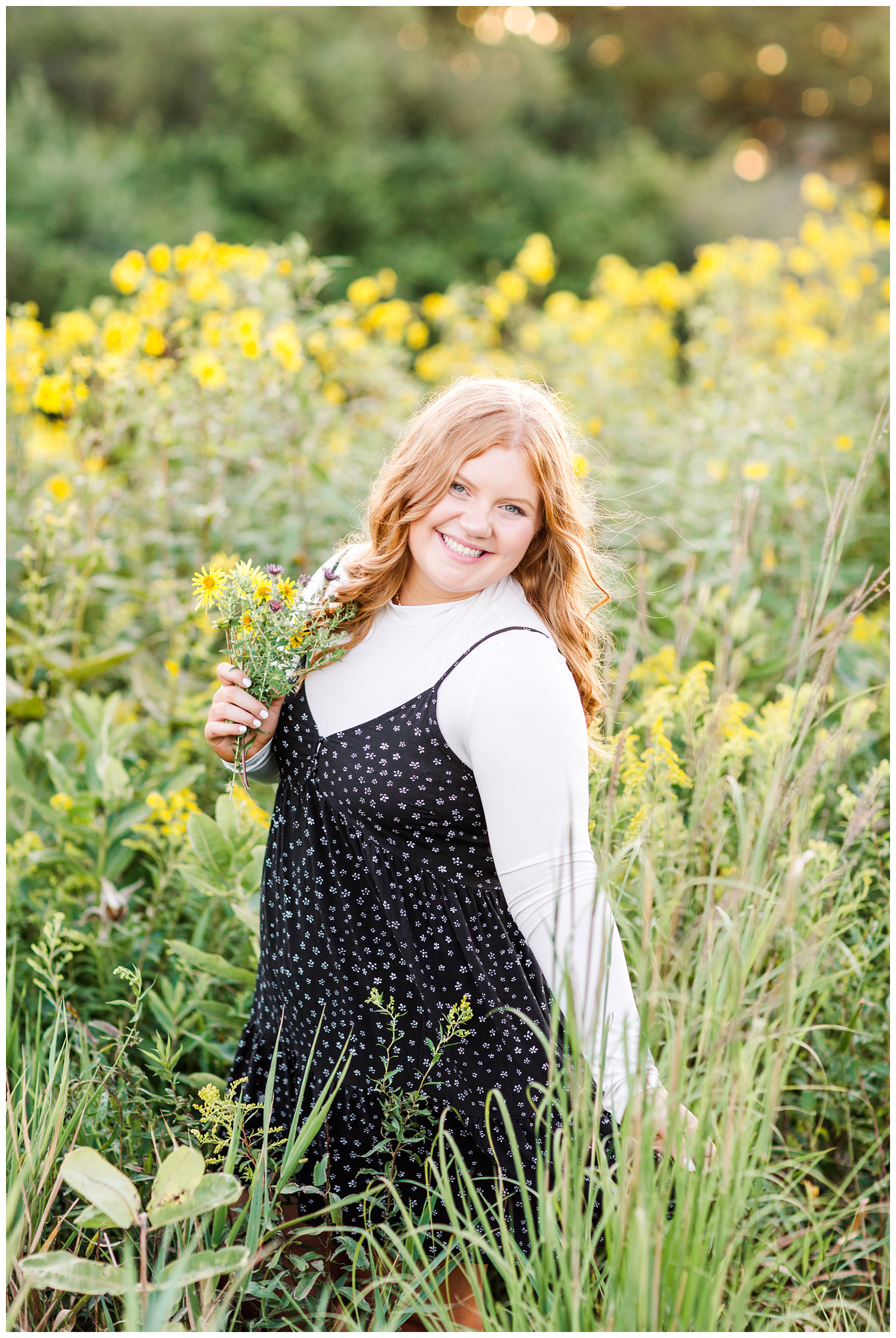 Senior girl wearing a black floral dress stands in a yellow flower field holding a flower bouquet at Water's Edge Nature Center in Algona, Iowa | CB Studio