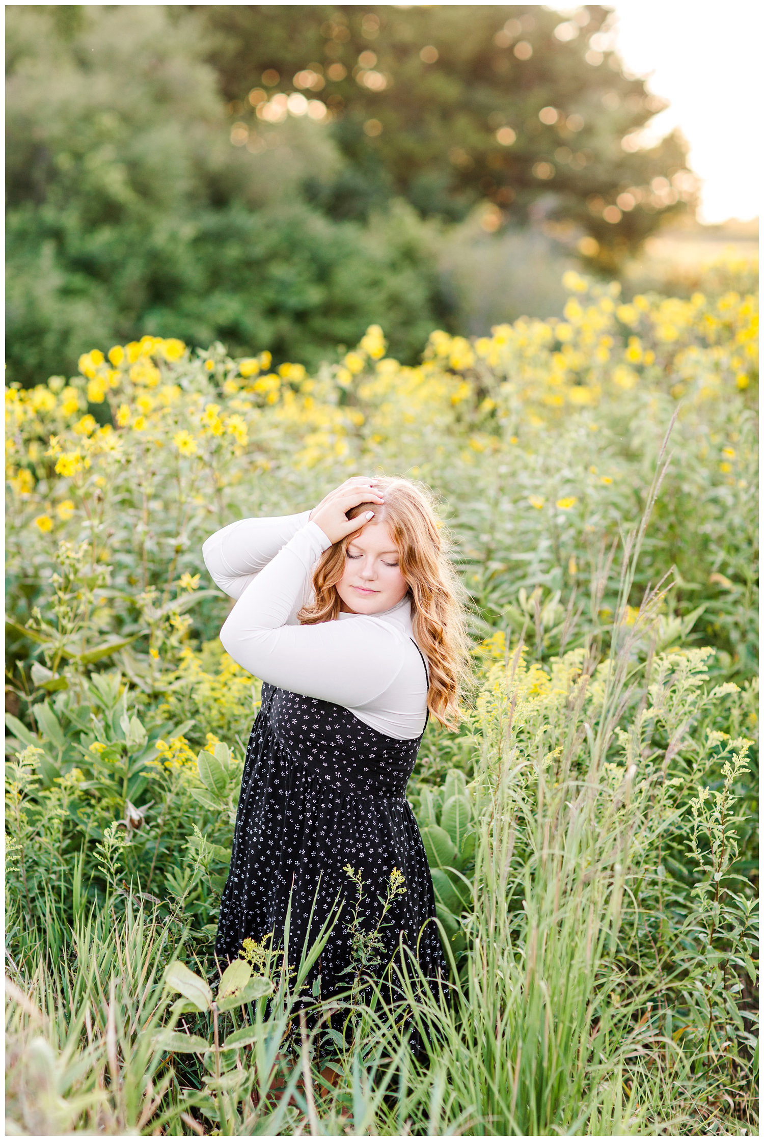 Senior girl wearing a black floral dress stands in a yellow flower field at Water's Edge Nature Center in Algona, Iowa | CB Studio