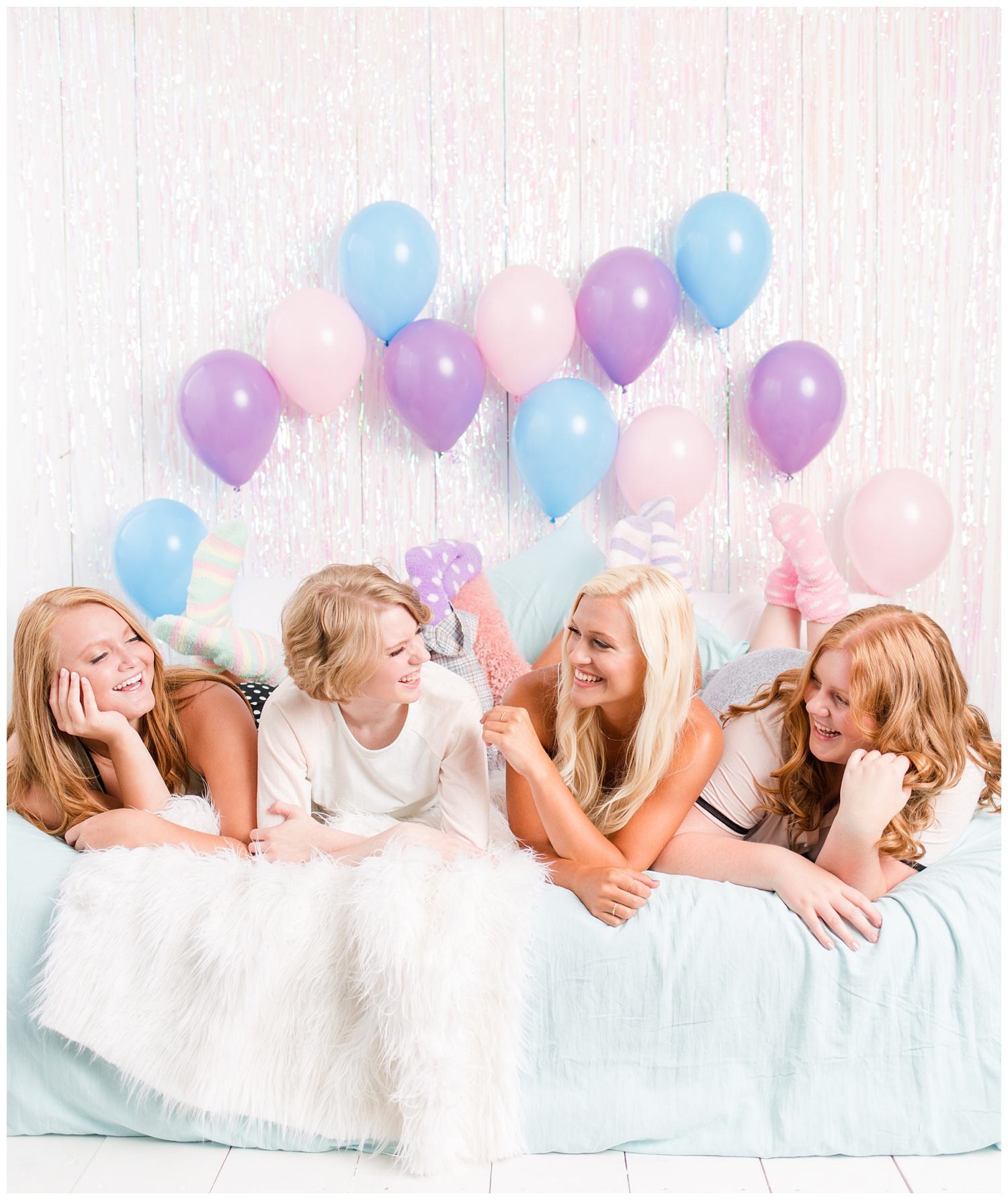 Senior girls laying on a bed and laughing during a senior sleepover-styled photoshoot with iridescent streamers and balloons. | CB Studio