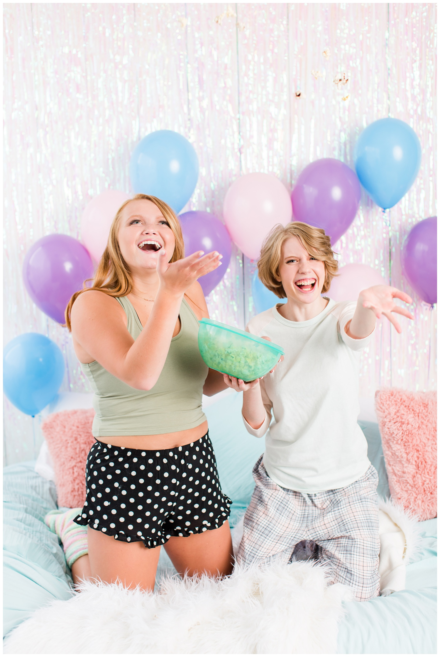 Senior girls throwing popcorn and laughing during a senior sleepover-styled photoshoot with iridescent streamers and balloons. | CB Studio