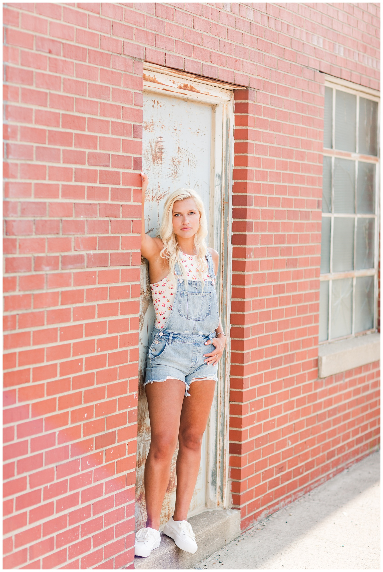 Senior girl wearing jean overalls leans against a rusty wall in downtown Algona, Iowa | CB Studio