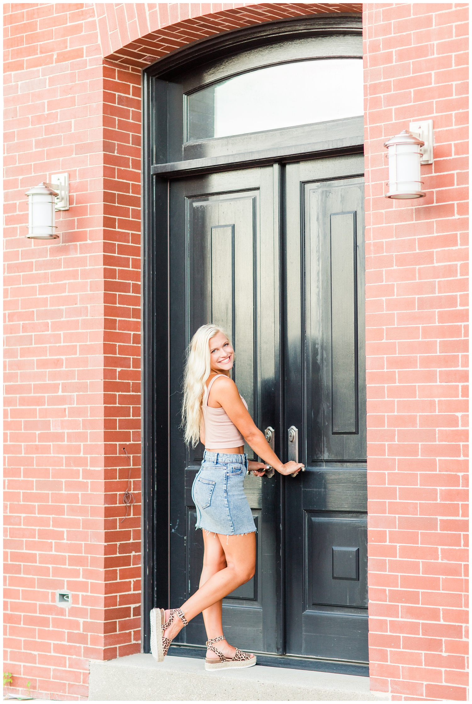Senior girl laughs as she's about to enter a historic brick building with tall black doors in downtown Algona, Iowa | CB Studio