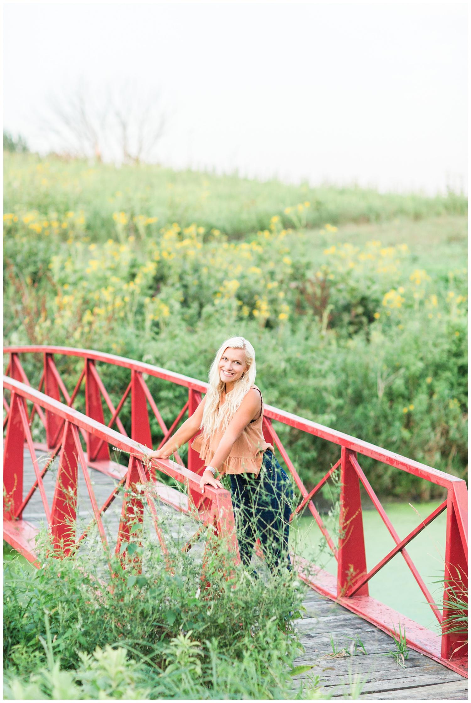 Senior girl standing on a red bridge at Water's Edge Nature Center in Algona, Iowa | CB Studio