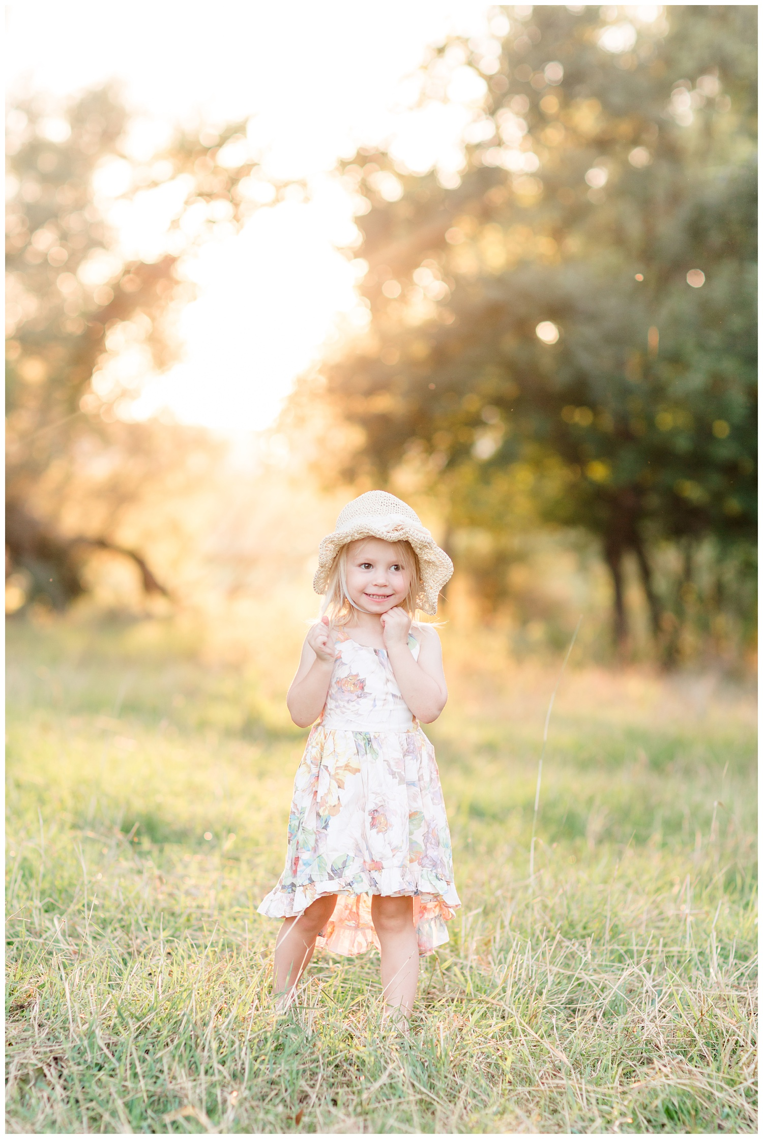 Little toddler girl wearing a floral dress and a straw hat dancing in a pasture during golden hour   CB Studio
