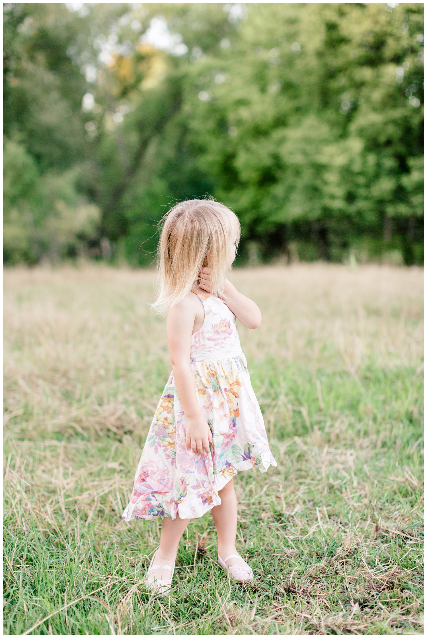 Little toddler girl wearing a floral dress looks off in the distance in a pasture during golden hour   CB Studio