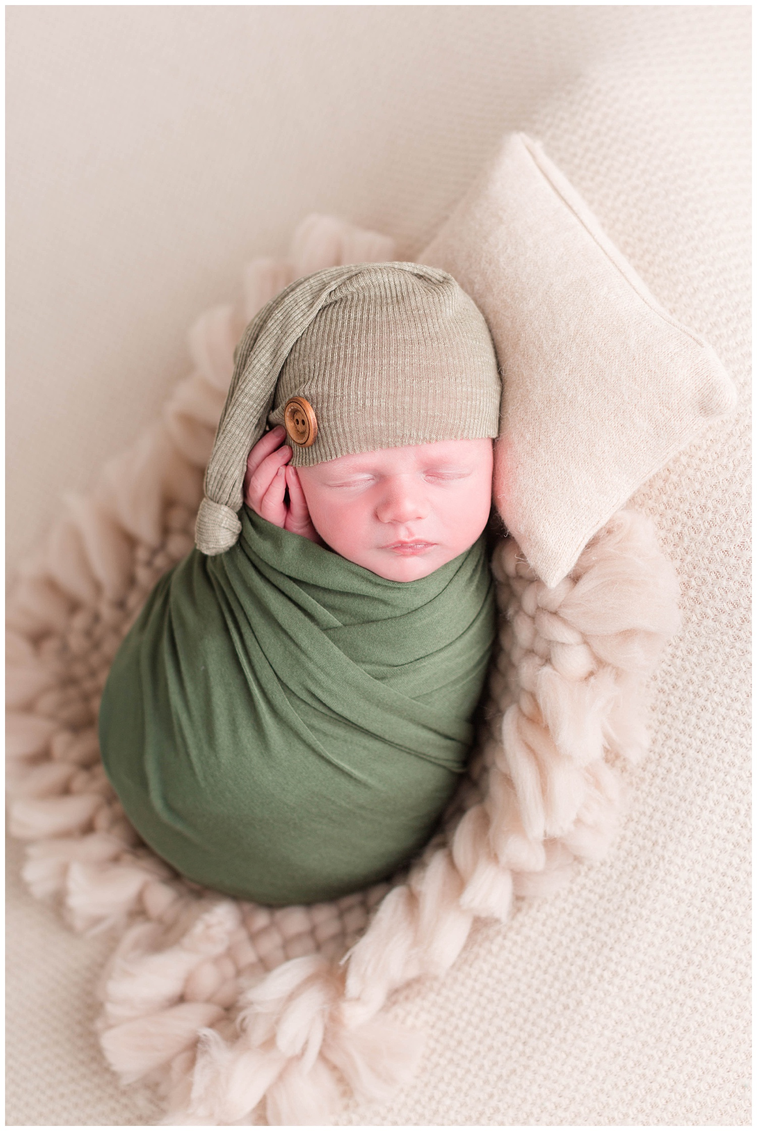 Newborn baby boy wrapped in a green swaddle wearing a green night cap with his hands gently folded along his cheek. | CB Studio