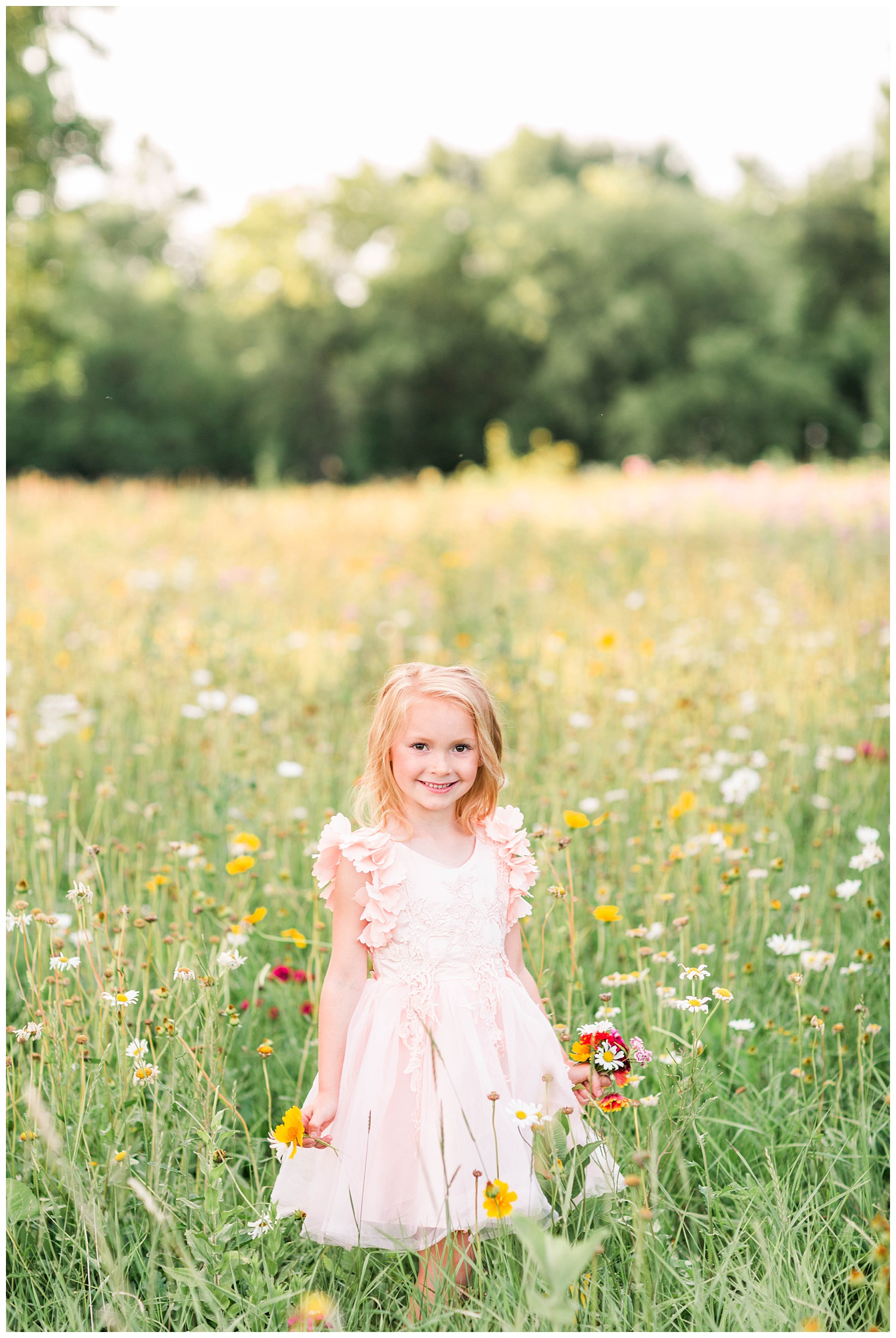Little Liella stands in a field of wild flowers holding a bouquet wearing tutu du monde couture dress by Trish Scully   CB Studio