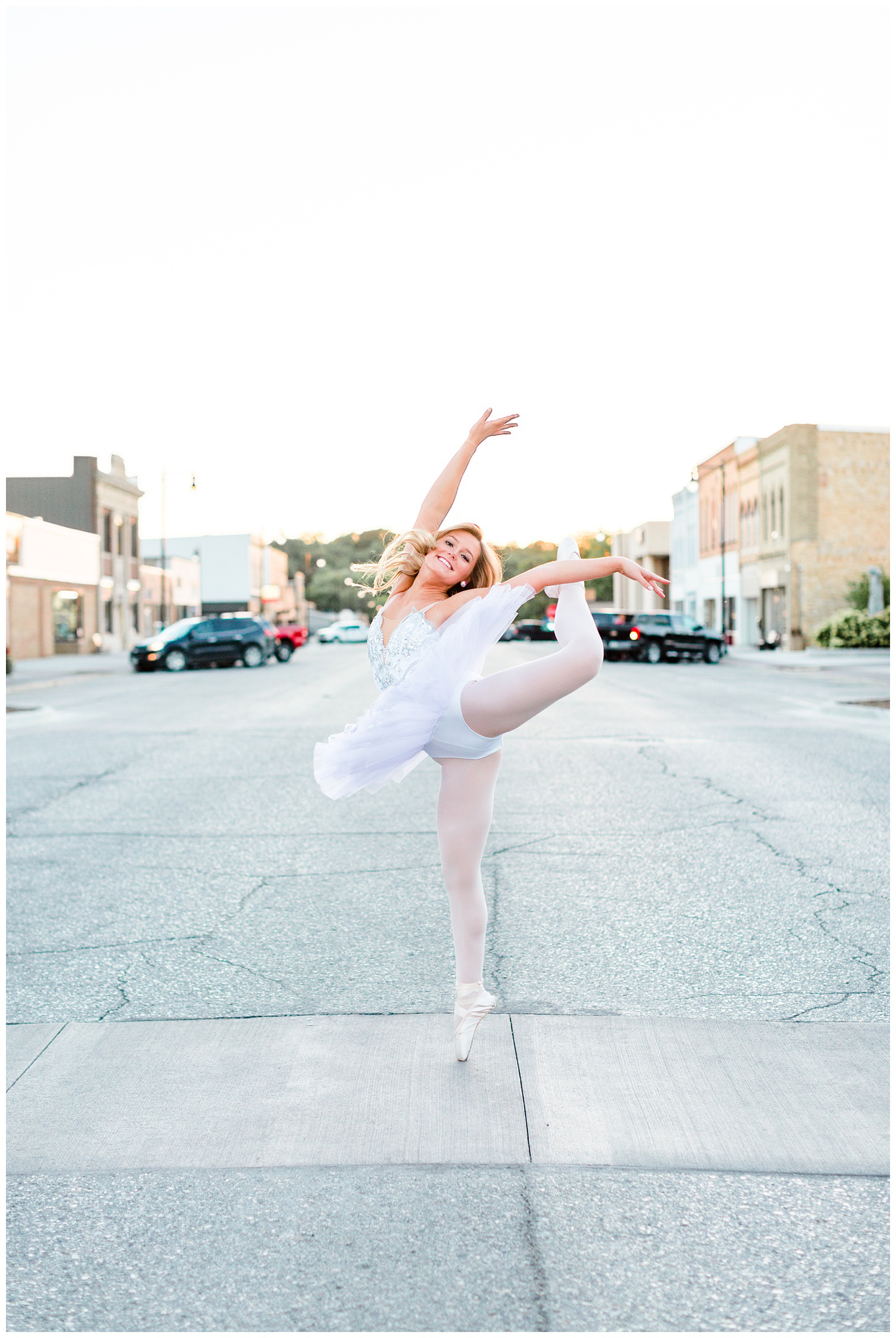 Senior dance photography girl performs an arabesque in full classical ballet white tutu in the middle of Sumner Ave in downtown Humboldt, Iowa | CB Studio