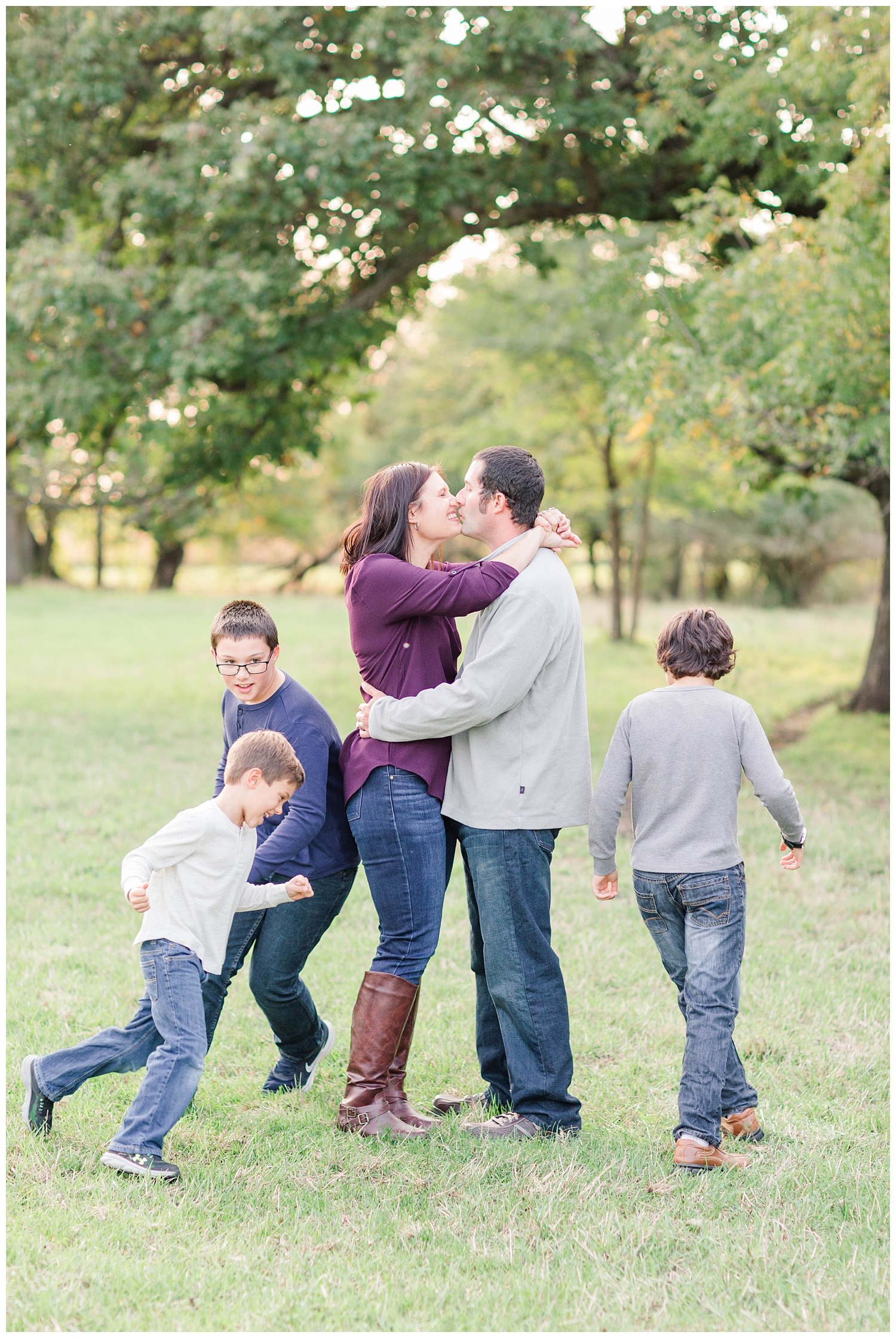 Mom and dad hug close for a kiss while the boys run around them in circles in a pasture in rural Iowa | CB Studio