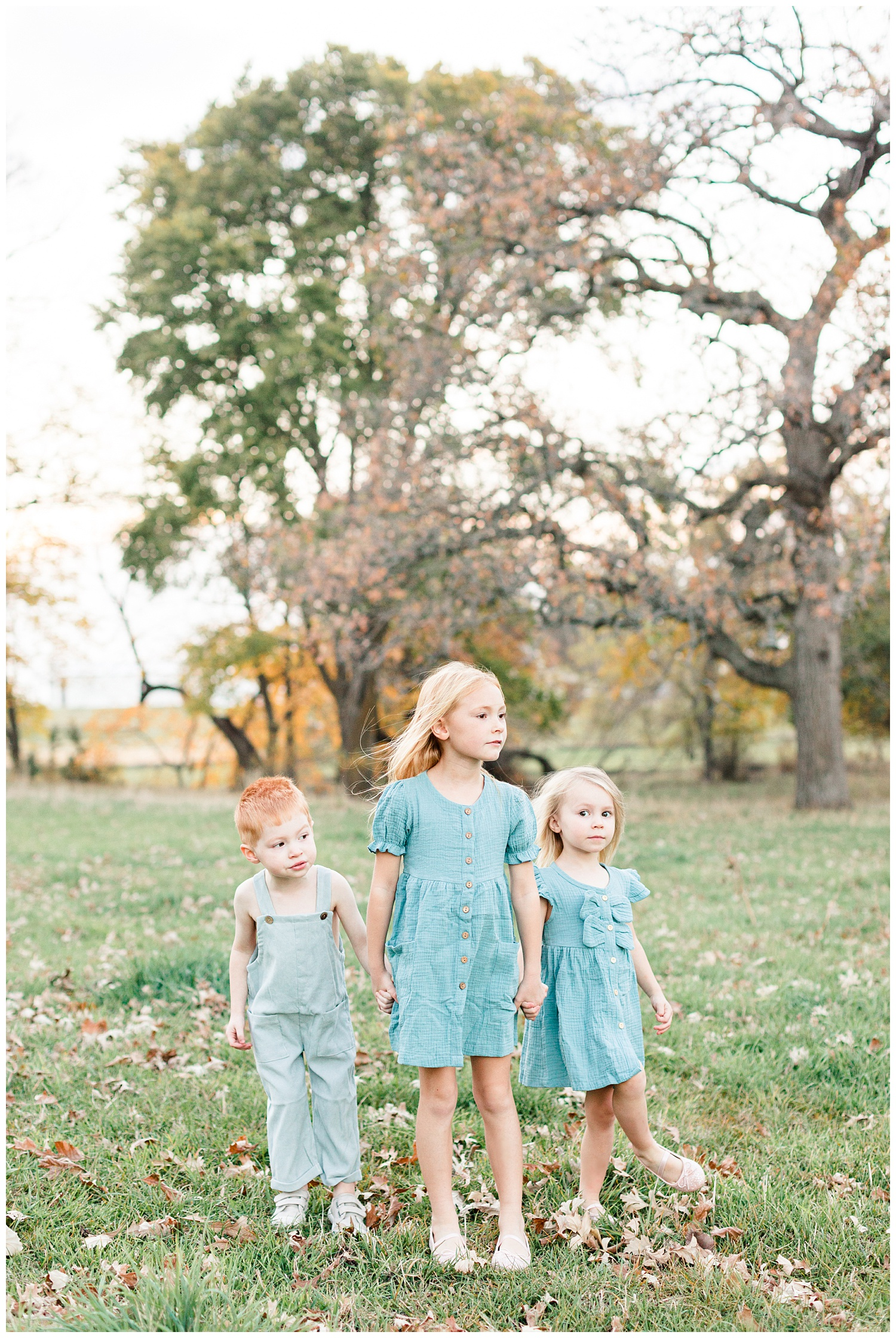 Three children dressed in vintage teal stand holding hands in a grassy field looking onward   CB Studio