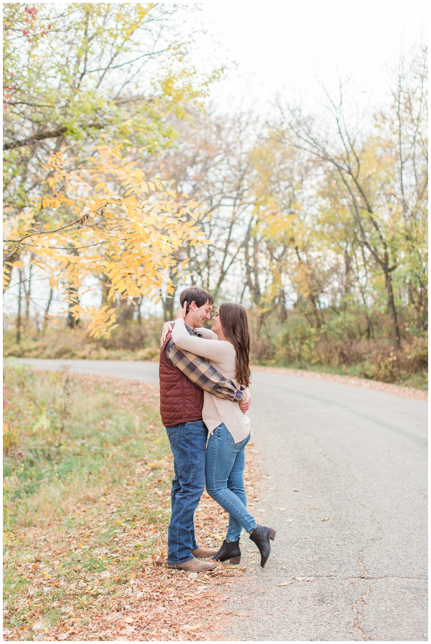 Fall in Iowa, Jenna embraces Brady in the middle of an autumn path at Lost Island Nature Center | CB Studio