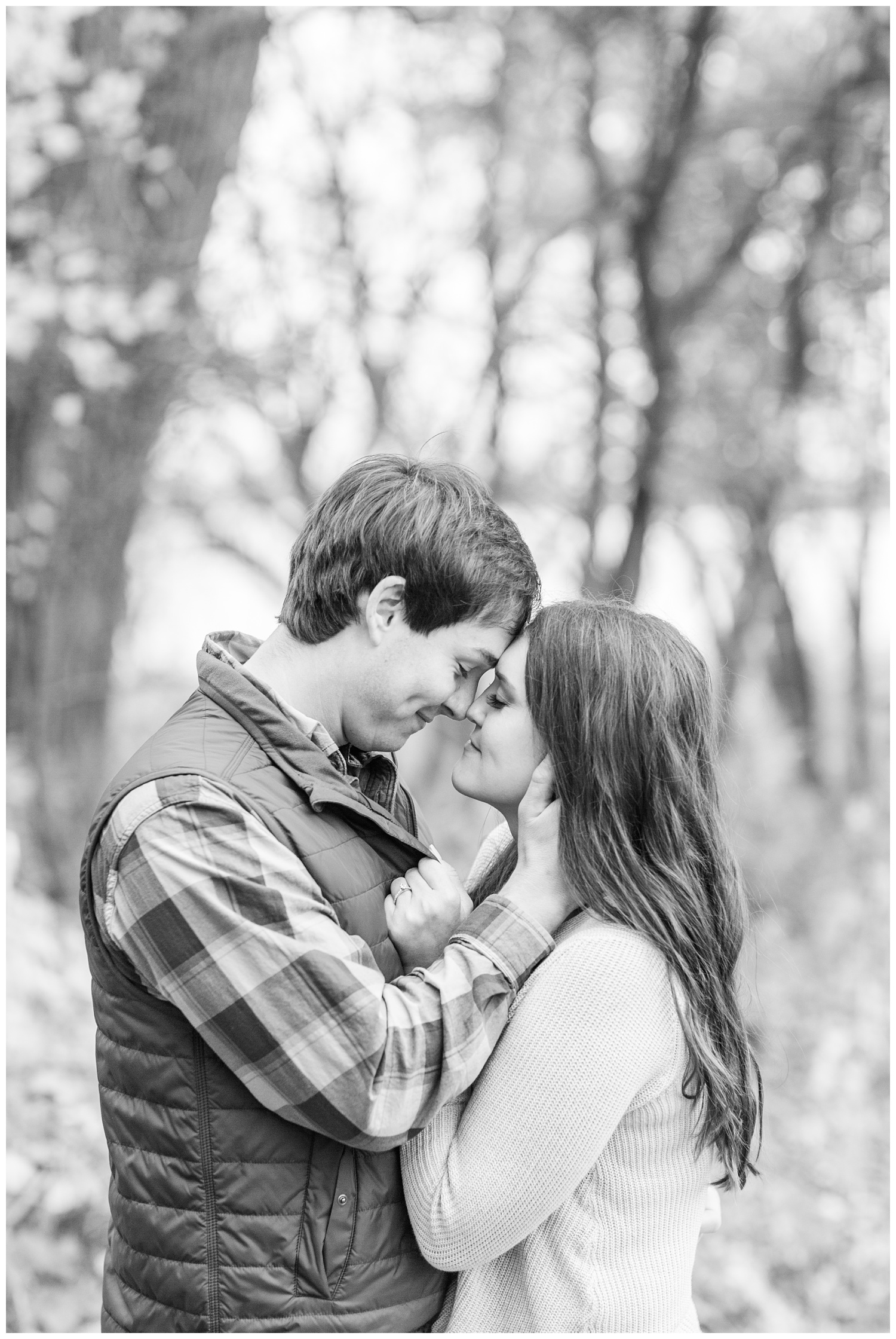 Fall in Iowa, Brady slowly pulls Jenna in for a kiss in the middle of an autumn path at Lost Island Nature Center | CB Studio