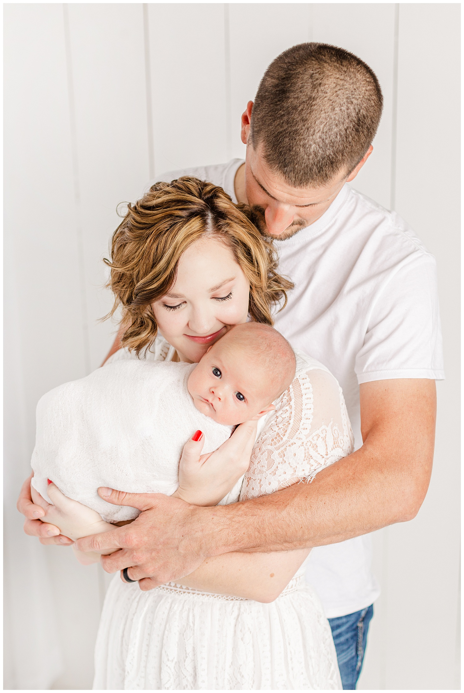 Bree and Josh dressed in white snuggle their new baby boy | CB Studio