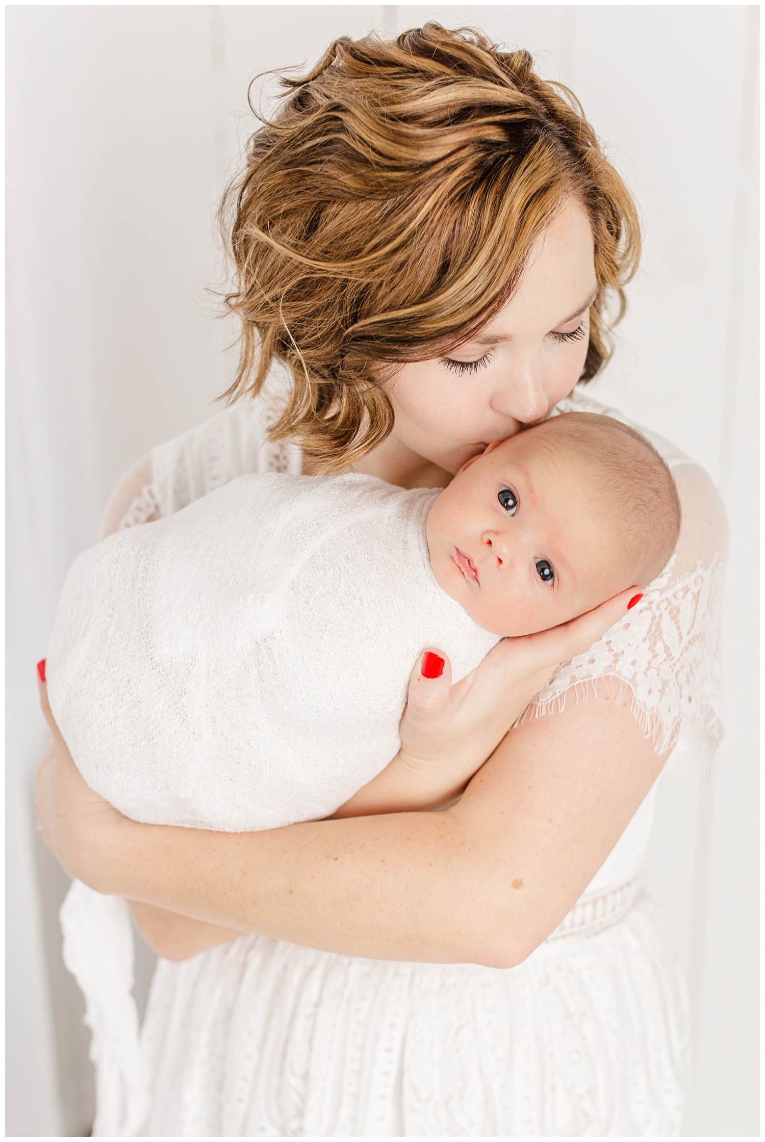 Bree dressed in white lace snuggles and gently kisses her new baby boy | CB Studio