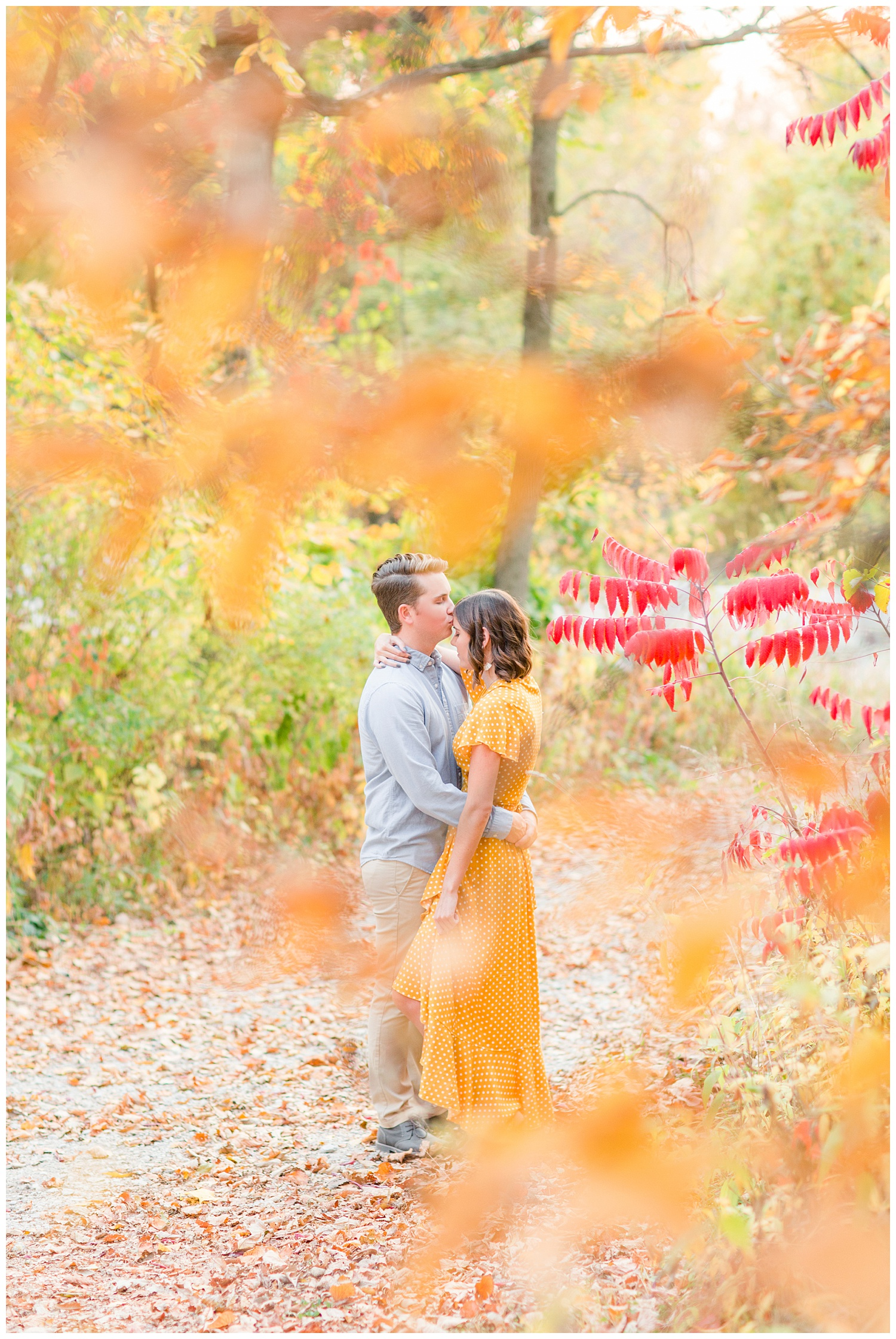 Luke kisses his girl on the forehead as they embrace in the middle of a fall wooded driveway | Iowa Wedding Photographer