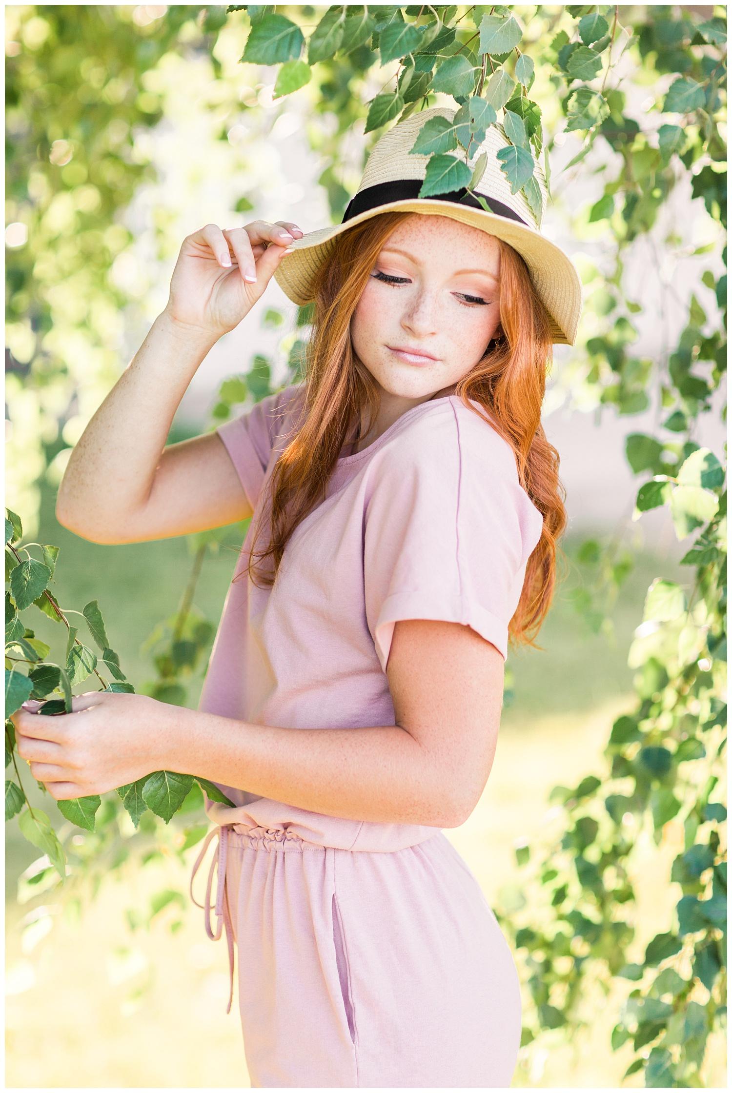 Senior Briley class of 2021 looks over her shoulder standing under a birch tree   Iowa Senior Photographer