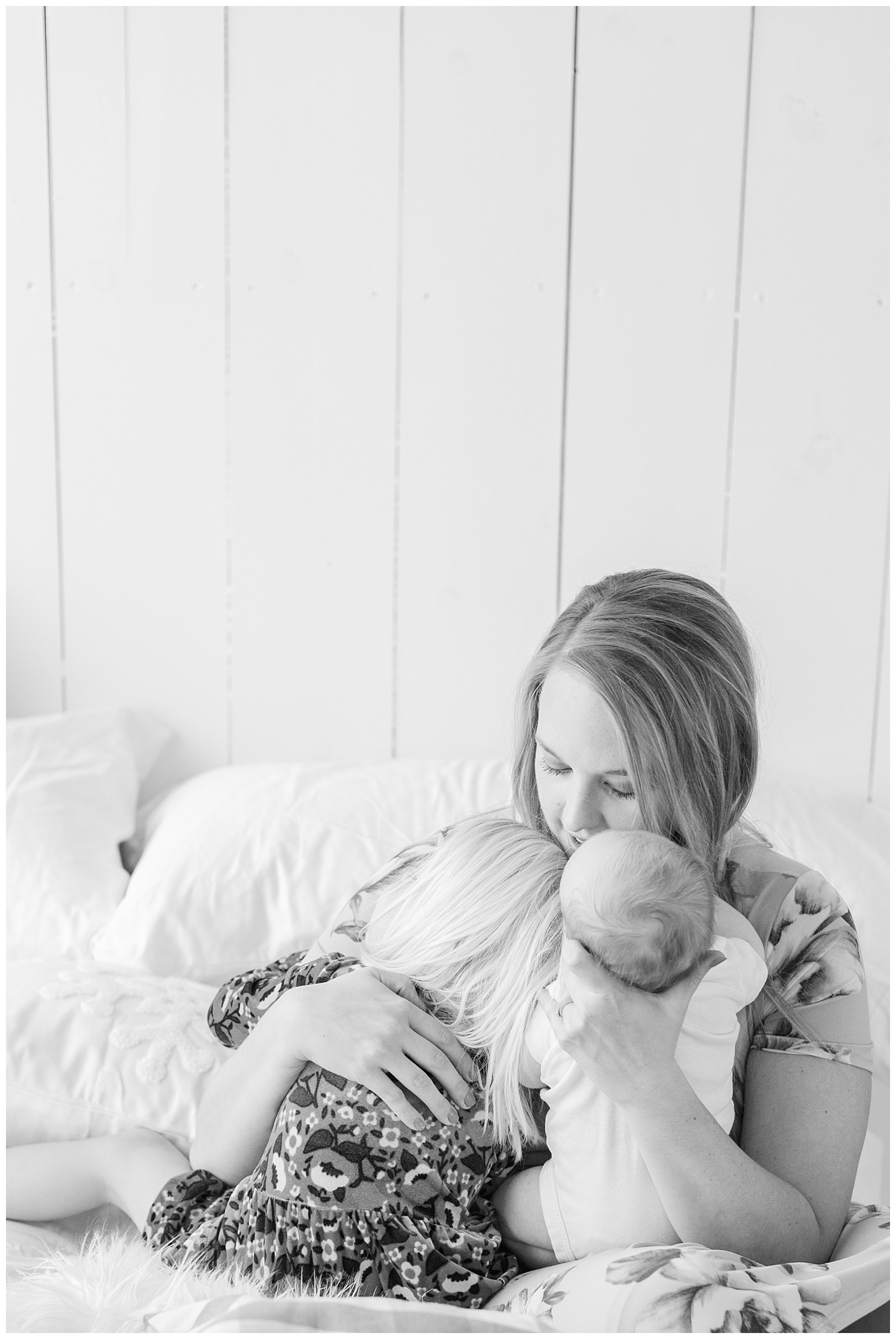 A mama snuggling her two babies during a snuggle photography session, her three year old toddler and newborn baby boy. | CB Studio